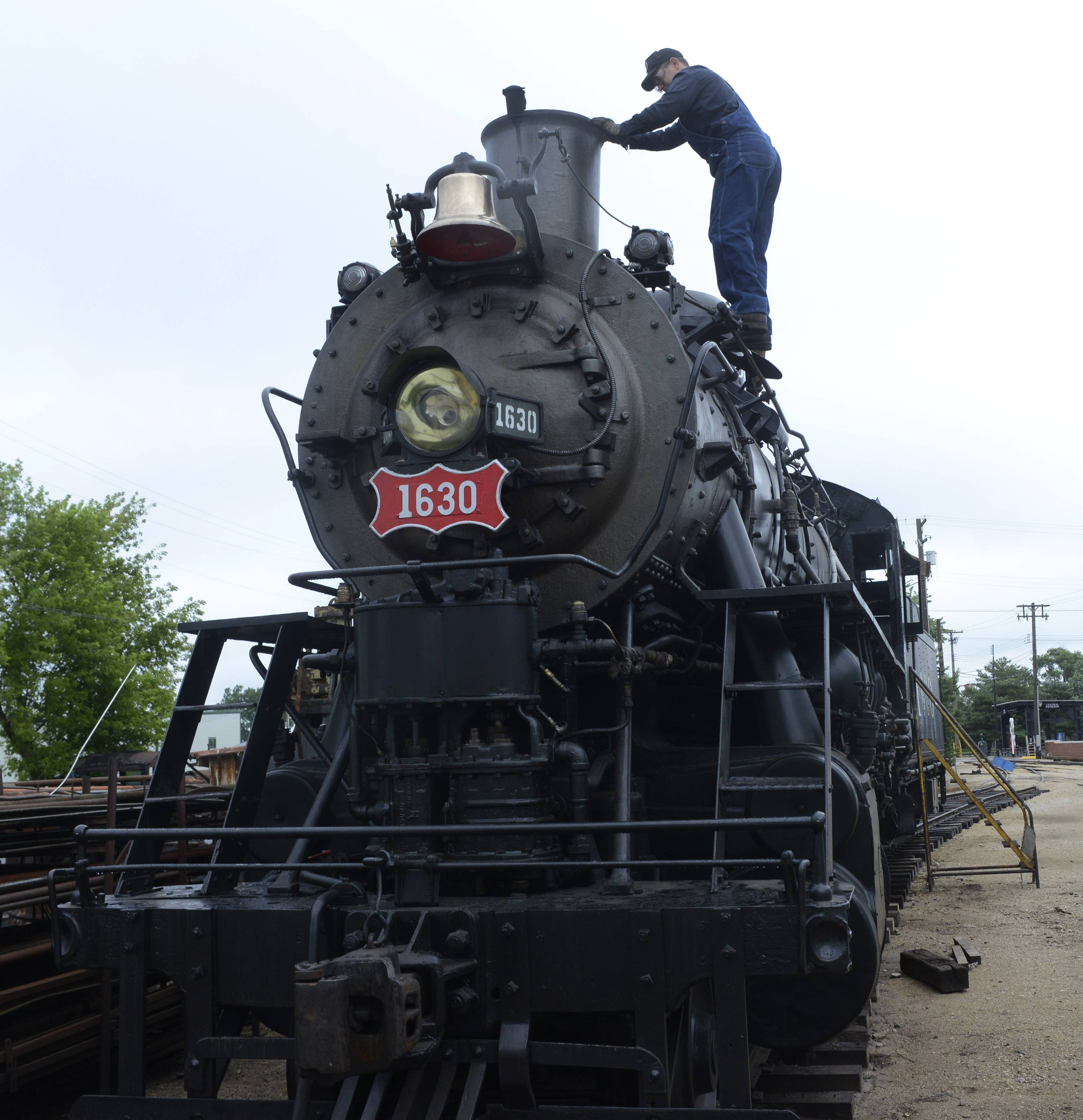 Elgin resident Jason Maxwell, a steam department volunteer at the Illinois Railway Museum in Union, starts the day by removing a cap, which is used to keep rain out of the exhaust stack of Frisco 1630.