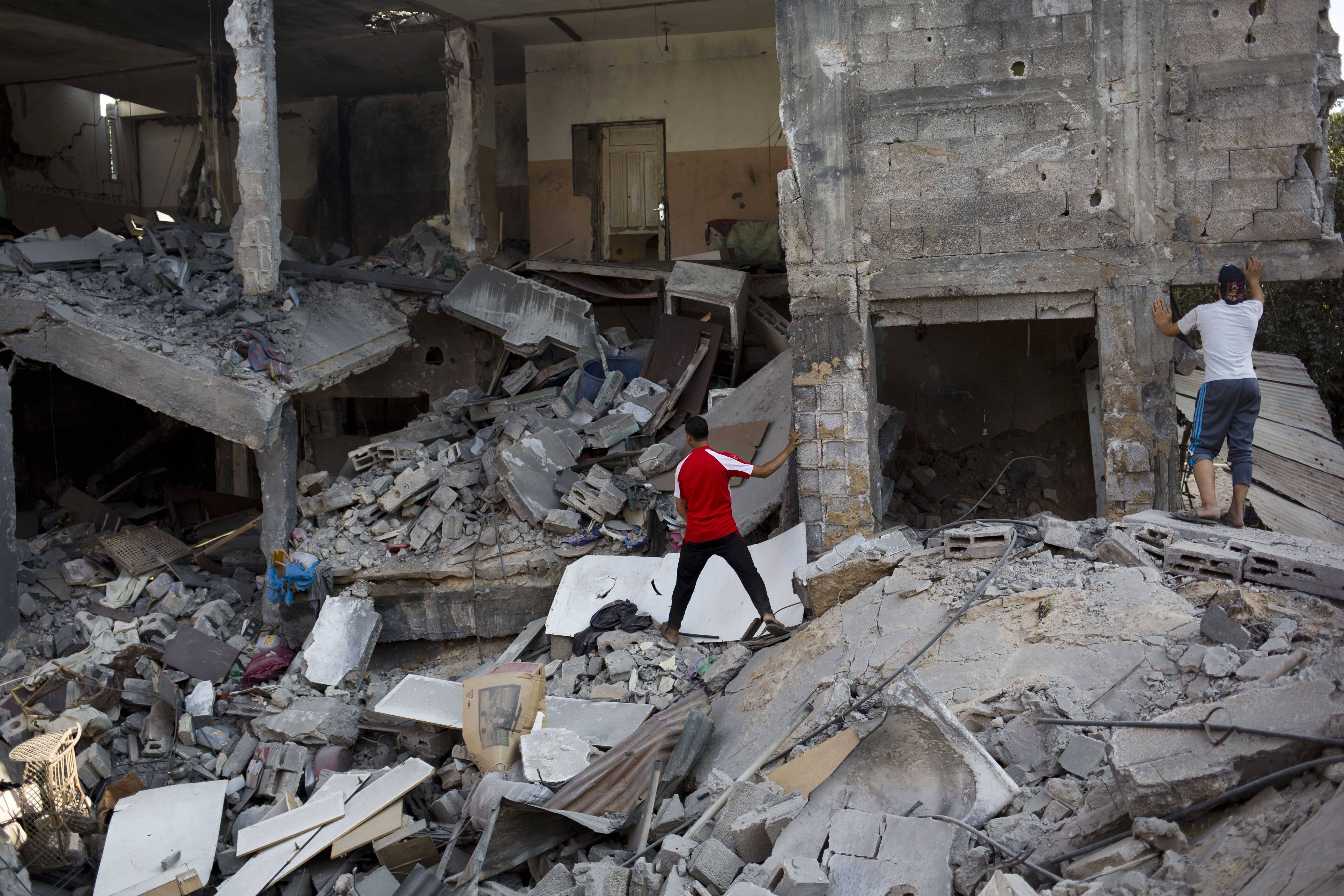 Palestinians inspect a destroyed house in the heavily bombed Gaza City neighborhood of Shijaiyah, close to the Israeli border, Friday, Aug. 1, 2014. A three-day Gaza cease-fire that began Friday quickly unraveled, with Israel and Hamas accusing each other of violating the truce.