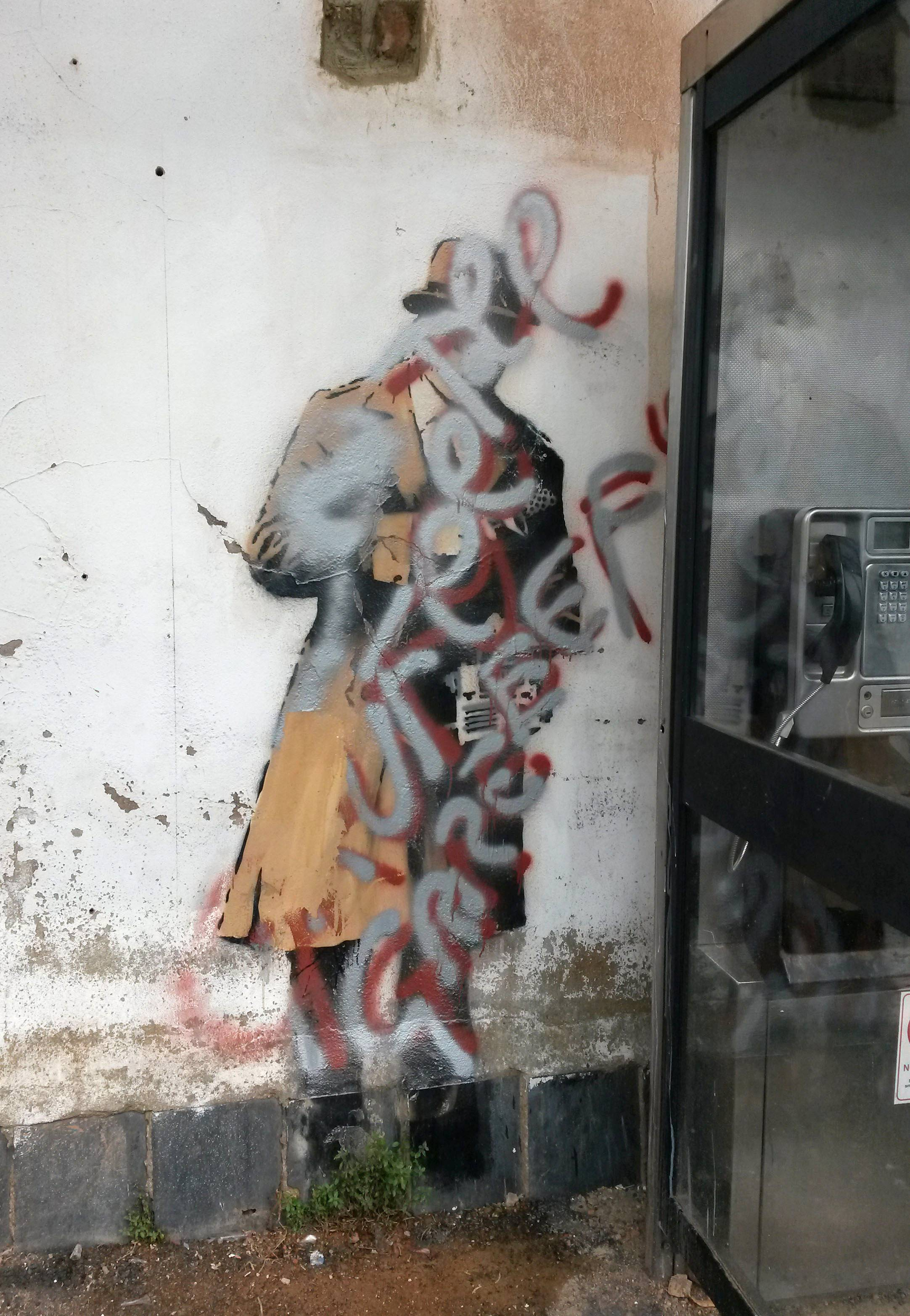 "The mural ""Spy Booth"" by street artist Banksy that sparked a local preservation campaign has been defaced with silver and red paint."