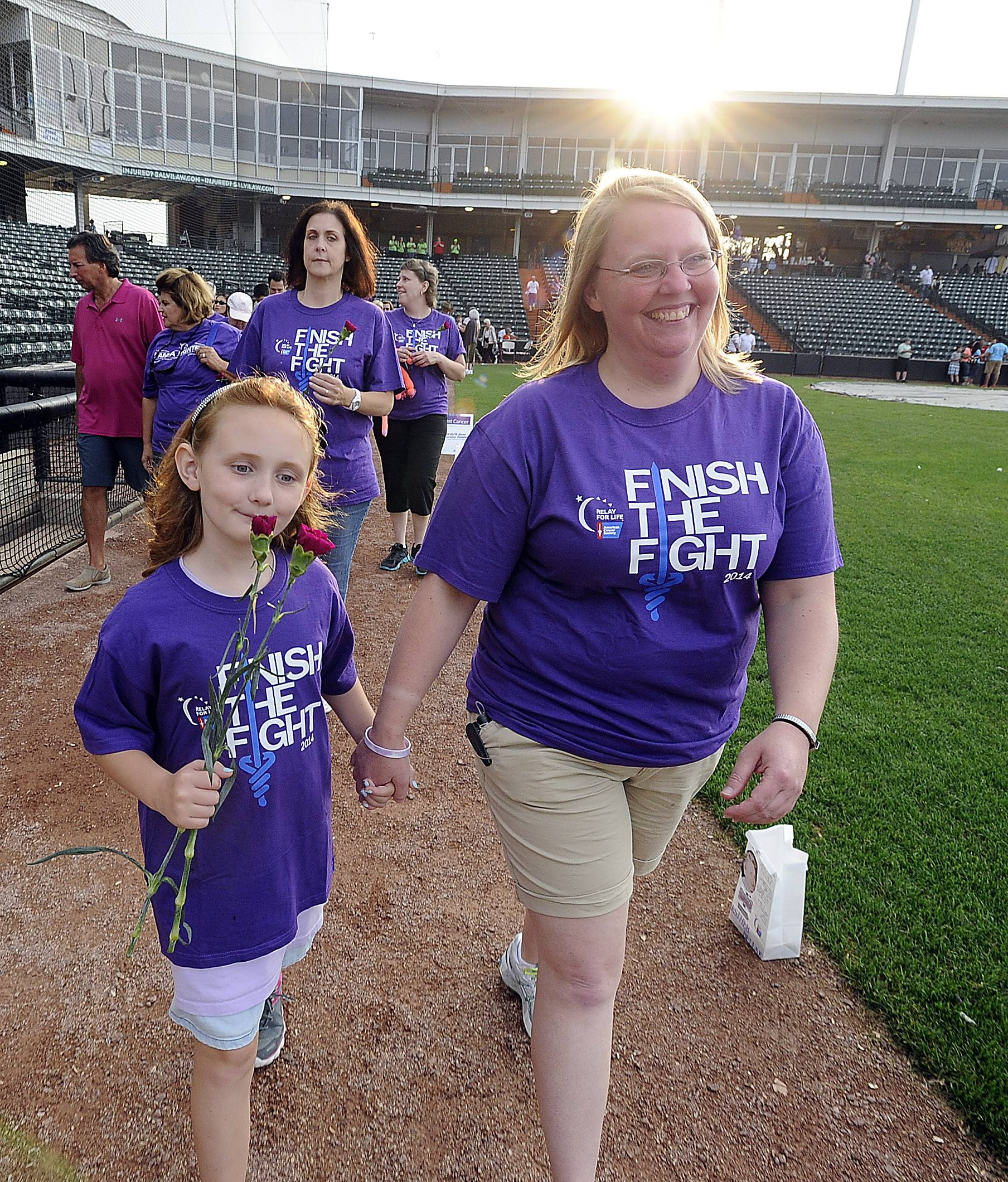 Carrie Horner of Palatine walks with her niece Ella Van Gheem , 8, of Gilberts in the annual Relay For Life at Boomers Stadium in Schaumburg on Friday. Horner is a 4 year survivor of colon cancer and Ella is a survivor of cancer for over a year.