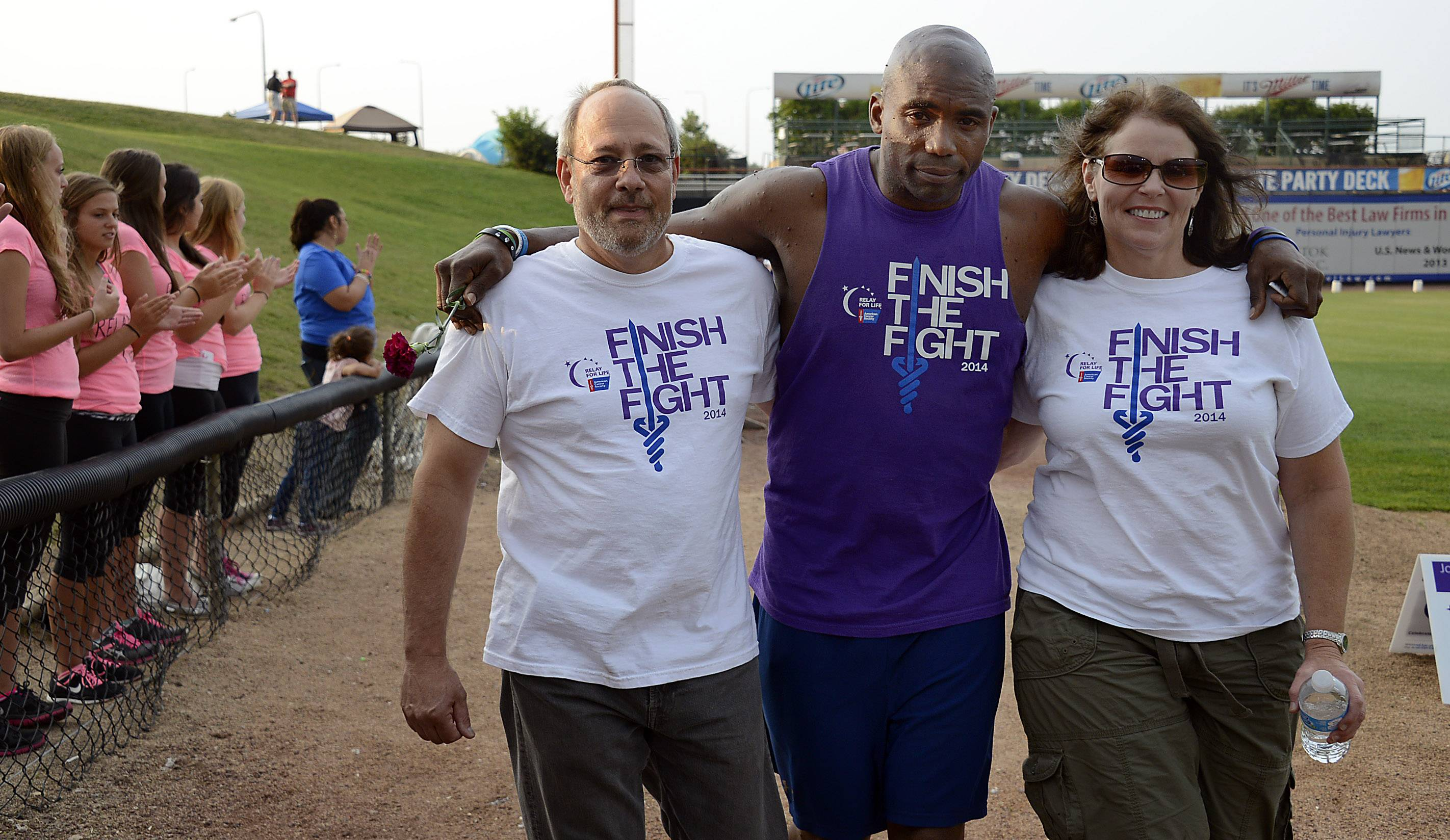 D. Anthony Evans of Schaumburg, center, and his cancer family Marcia Singery of Elgin and Don Larsen of Schaumburg walk with him at the annual Relay for Life at Boomers Stadium on Friday.  Evans has had over 9 operations in 22 months for tumors that are brought on by his neurofibomatosis.