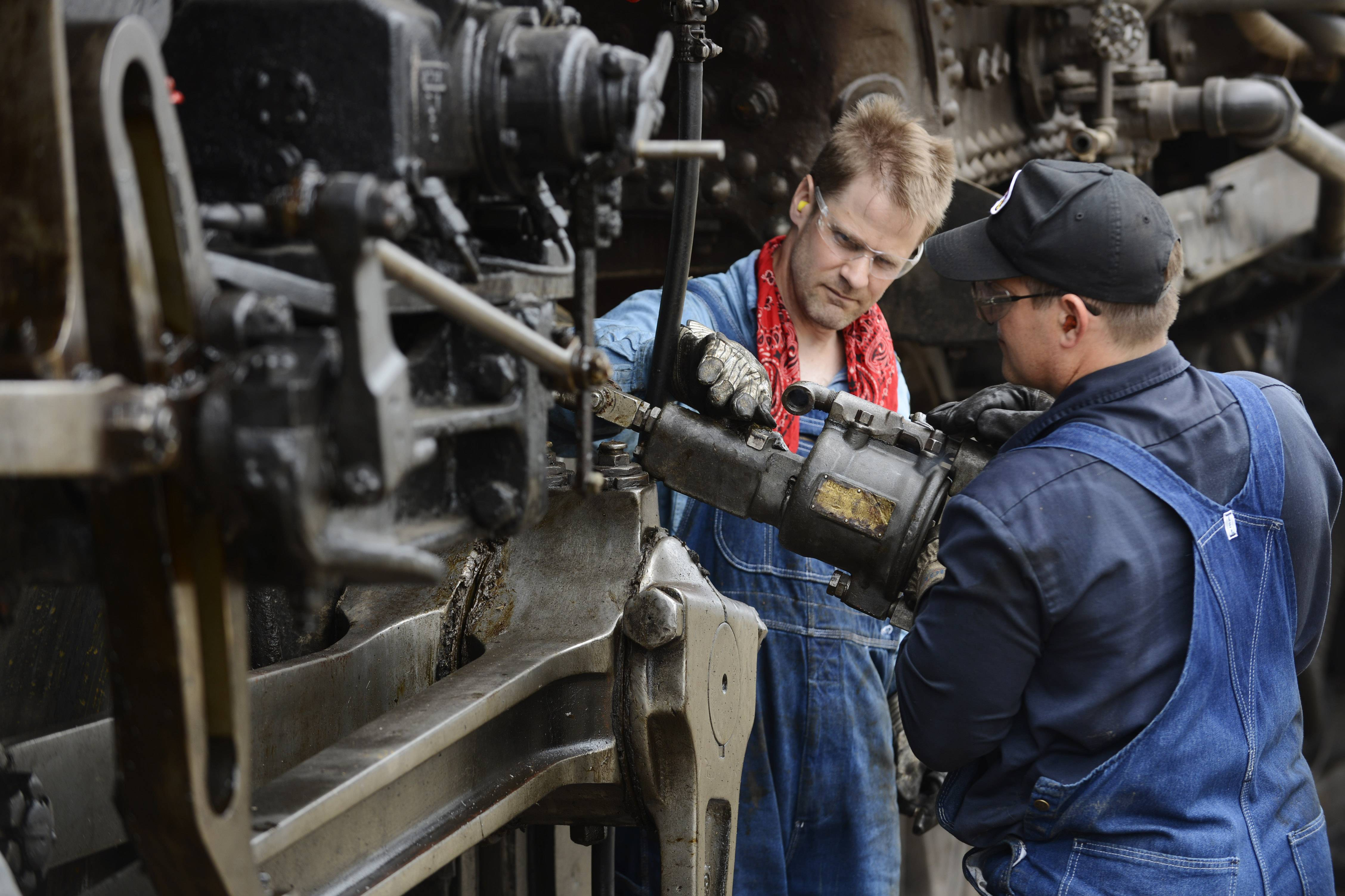 Student fireman Eric Wahlmark, left, of Aurora checks grease fittings with Maxwell on Frisco 1630 at the Illinois Railway Museum in Union.