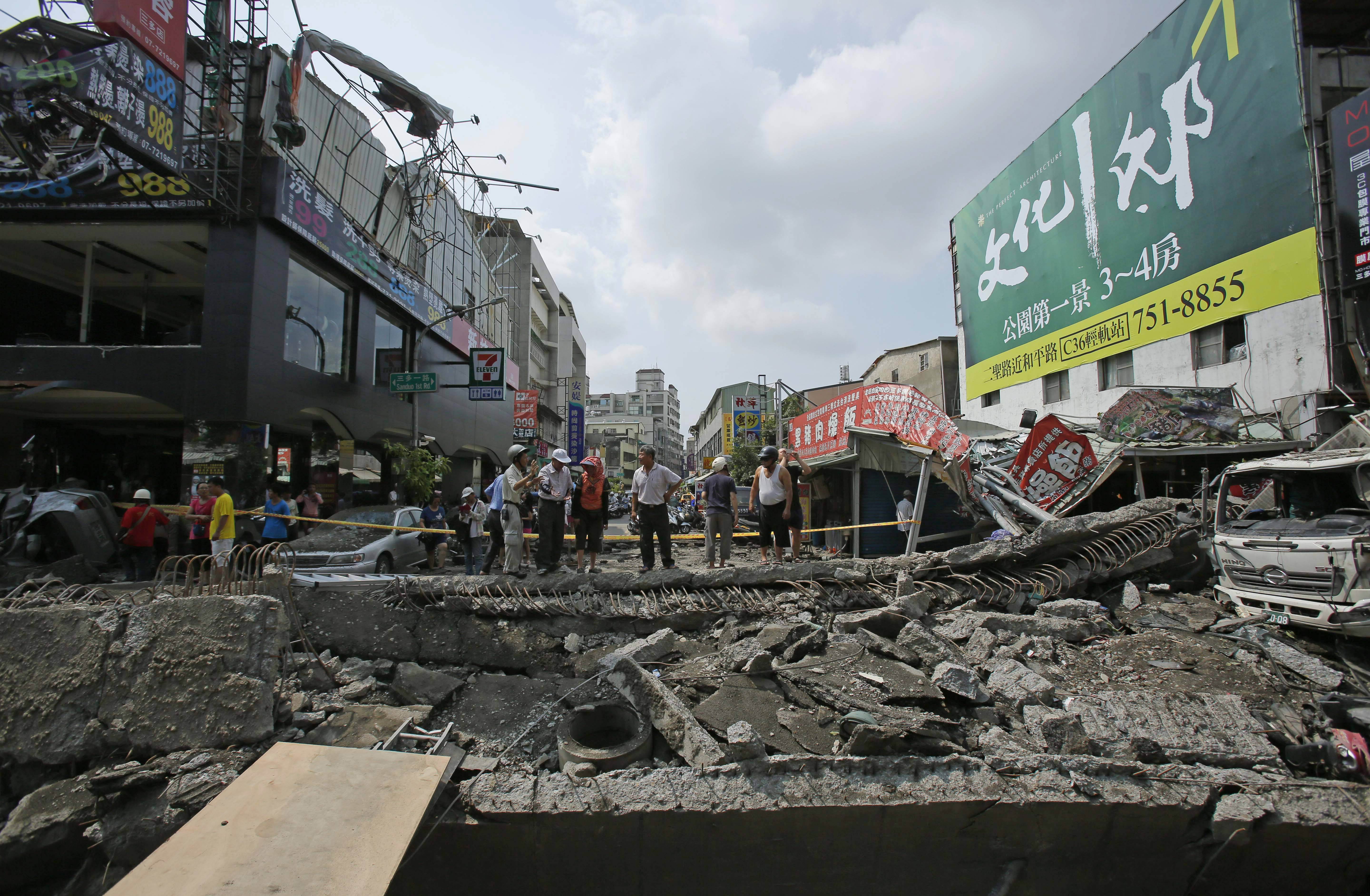 Locals survey the damage from a massive gas explosion in Kaohsiung, Taiwan, Friday, Aug. 1, 2014.