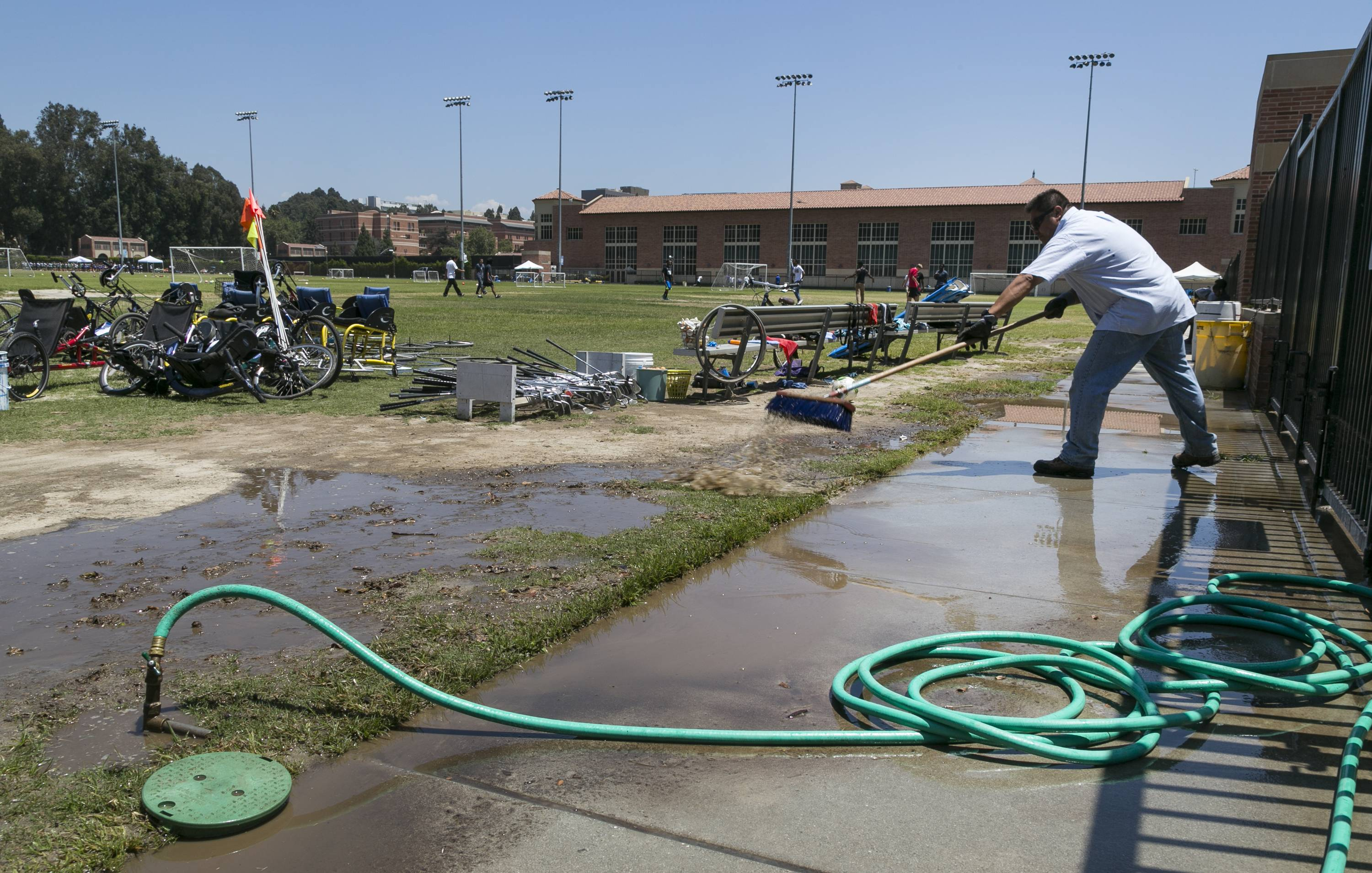 UCLA facilities management worker Hector Tovar cleans the IM Field Thursday after Tuesday's flooding from a ruptured pipe under nearby Sunset Boulevard inundated a large area of the campus in the Westwood section of Los Angeles.