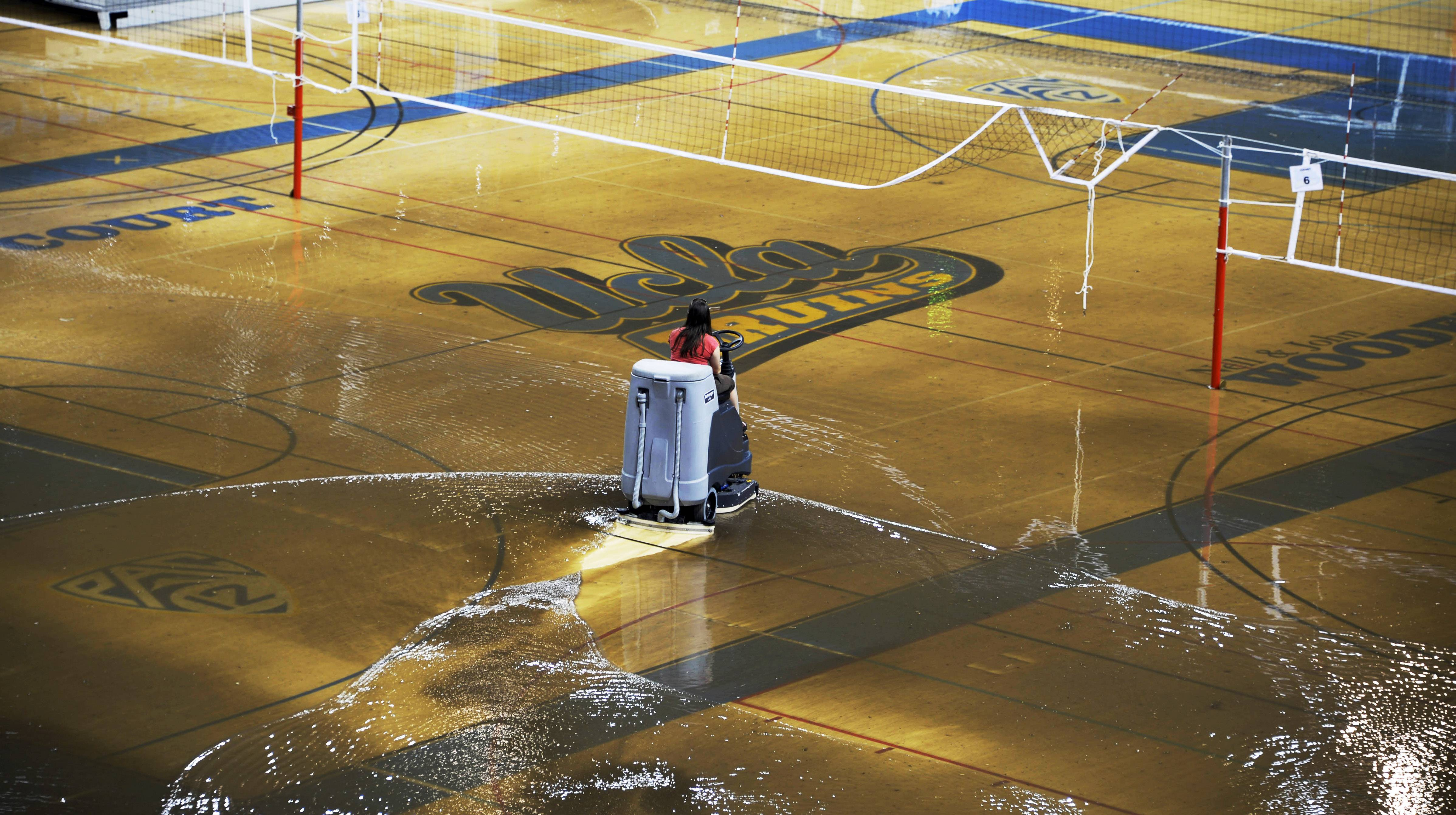 A worker begins the task of cleaning up at least an inch of water covering the playing floor at Pauley Pavilion, home of UCLA basketball, after a broken 30-inch water main under nearby Sunset Boulevard caused flooding Tuesday that inundated several areas of the UCLA campus in the Westwood section of Los Angeles.