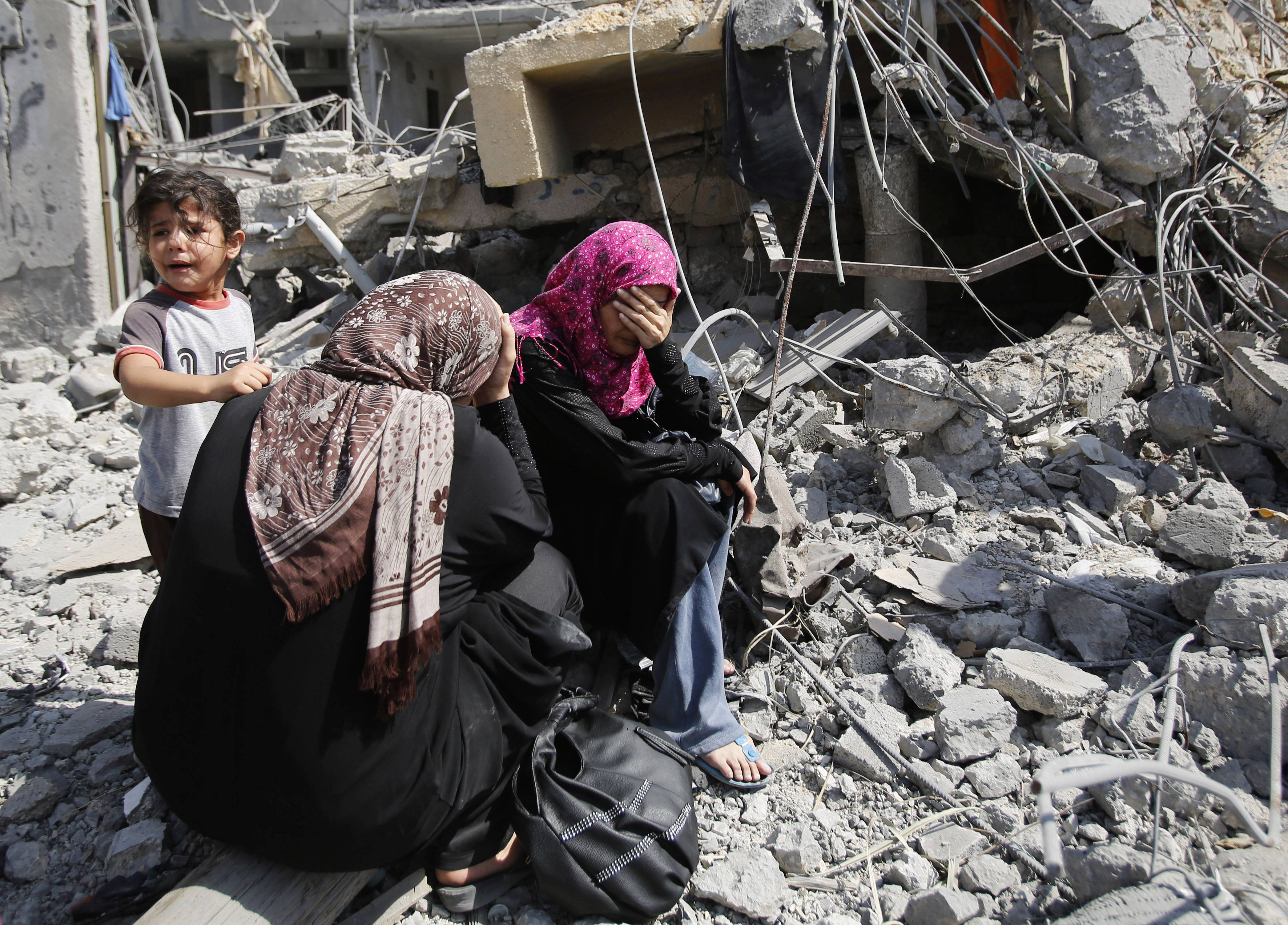 Palestinian women sit Friday on the rubble of their home in Beit Hanoun, Gaza Strip. A three-day Gaza cease-fire that began Friday quickly unraveled, with Israel and Hamas accusing each other of violating the truce.
