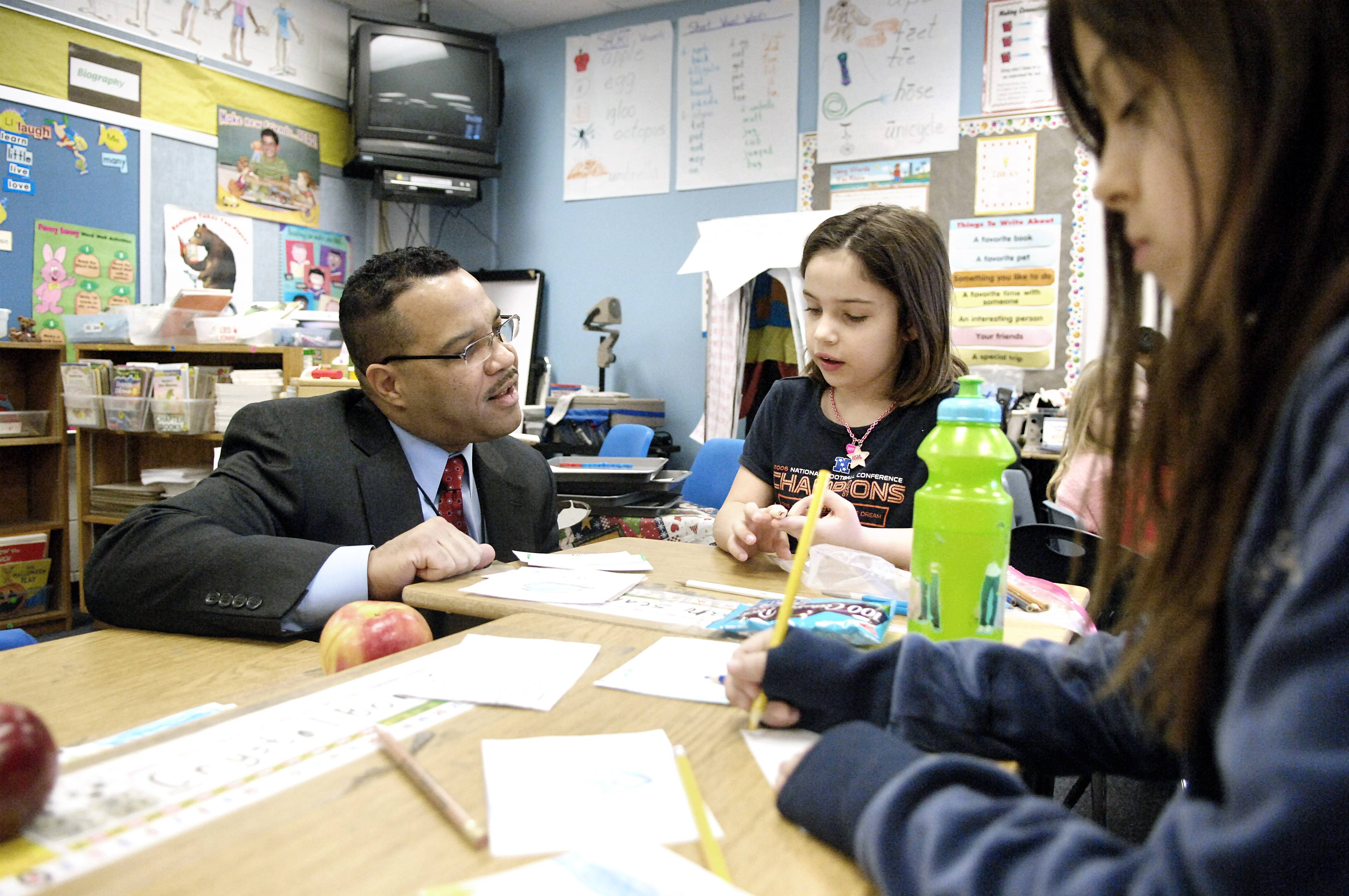 U-46 Superintendent Jose Torres learns from second-grader Marian Stanek about the vocabulary/geography lesson her class was doing at Hillcrest Elementary School in Elgin in 2009.
