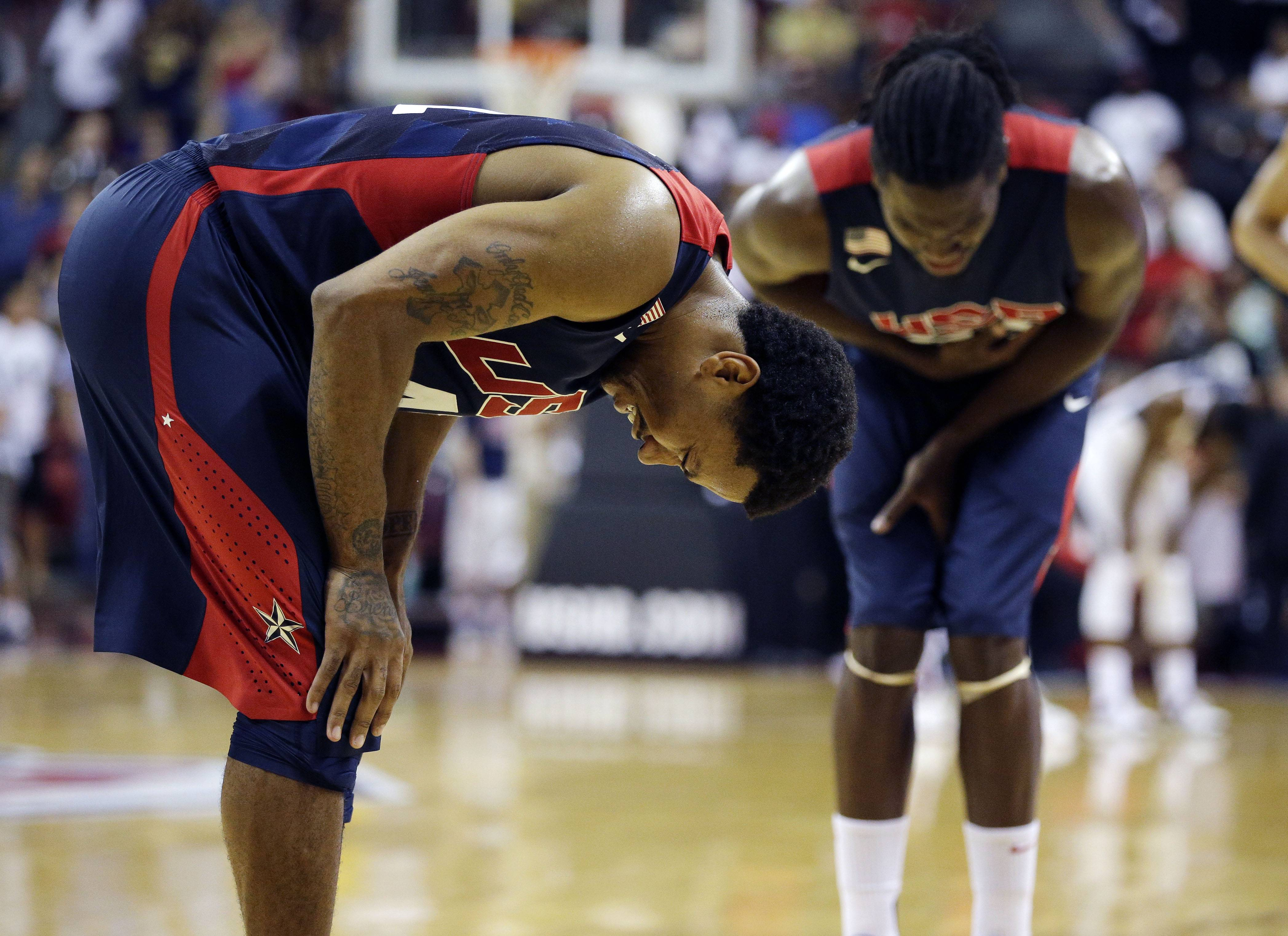 Chicago Bulls' Derrick Rose, left, and Denver Nuggets' Kenneth Faried, right, react after seeing Indiana Pacers' Paul George get injured during the USA Basketball Showcase game Friday, Aug. 1, 2014, in Las Vegas.