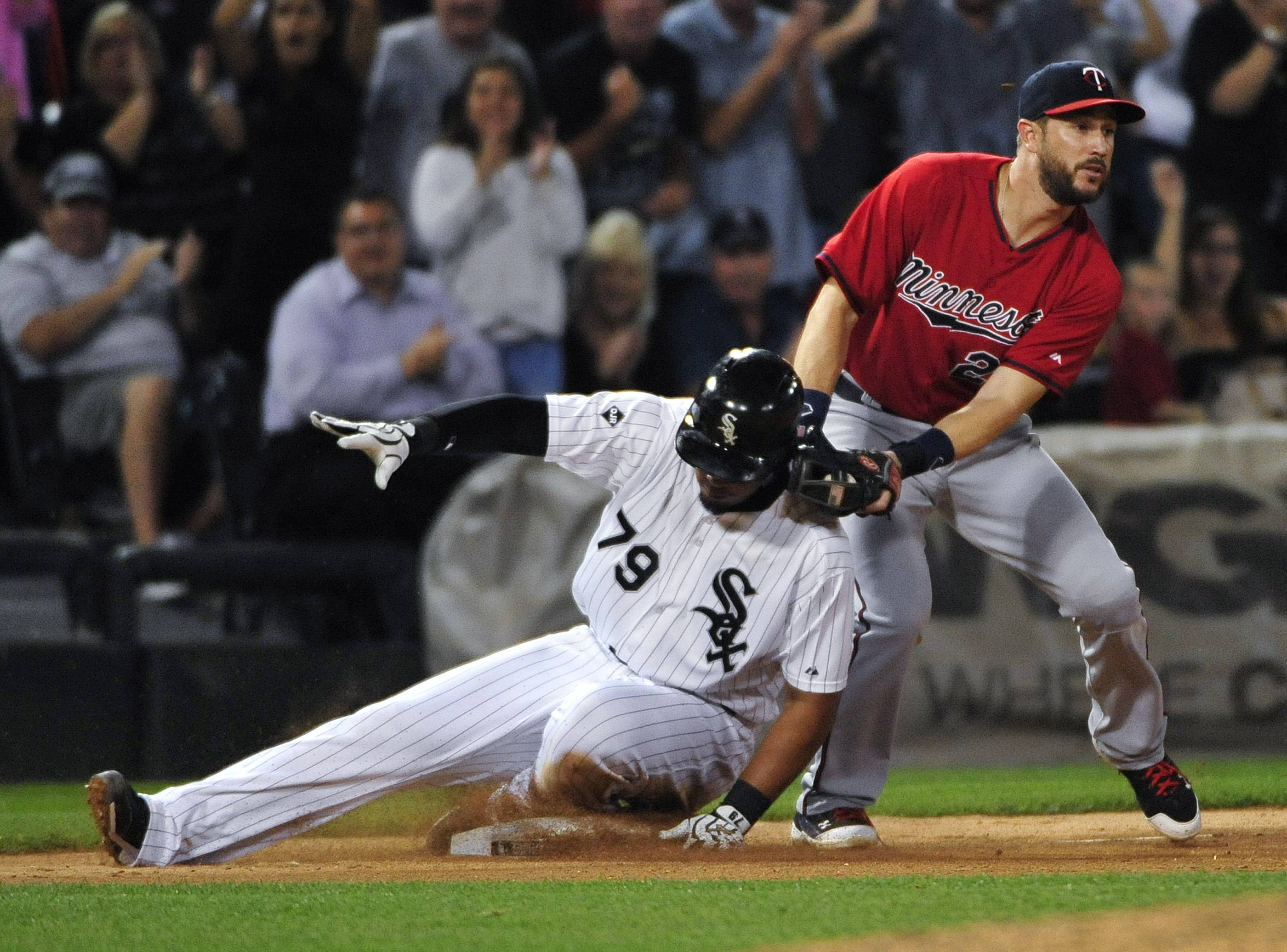 The White Sox's Jose Abreu (79) slides safely into third base as Minnesota Twins third baseman Trevor Plouffe makes a late tag during the eighth inning of a baseball game, Friday, Aug. 1, 2014, in Chicago.