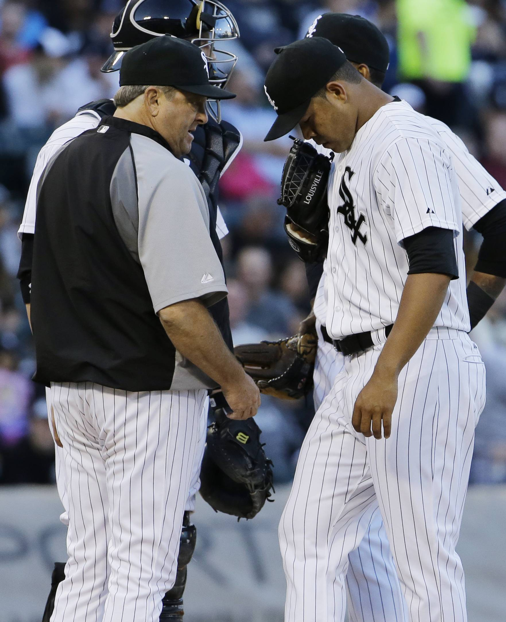 White Sox starter Jose Quintana, right, looks down as he listens to pitching coach Don Cooper during the first inning of a baseball game against the Kansas City Royals in Chicago on Friday, June 13, 2014.