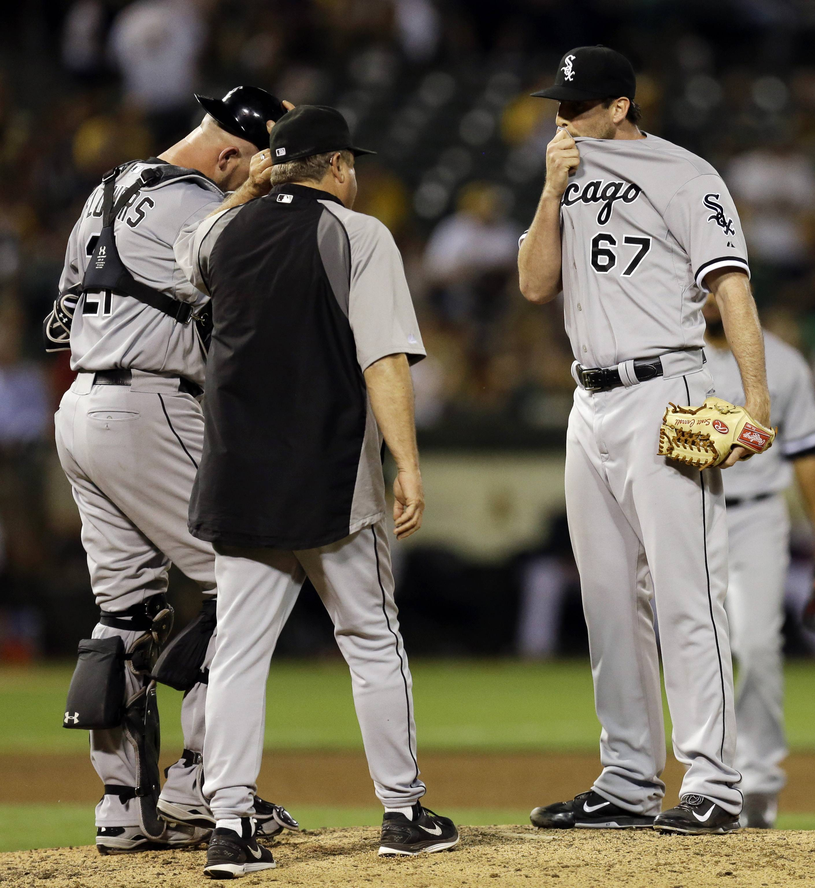 White Sox pitcher Scott Carroll (67) is visited on the pitching mound by coach Don Cooper in the fifth inning of a baseball game against the Oakland Athletics, Tuesday, May 13, 2014, in Oakland, Calif.