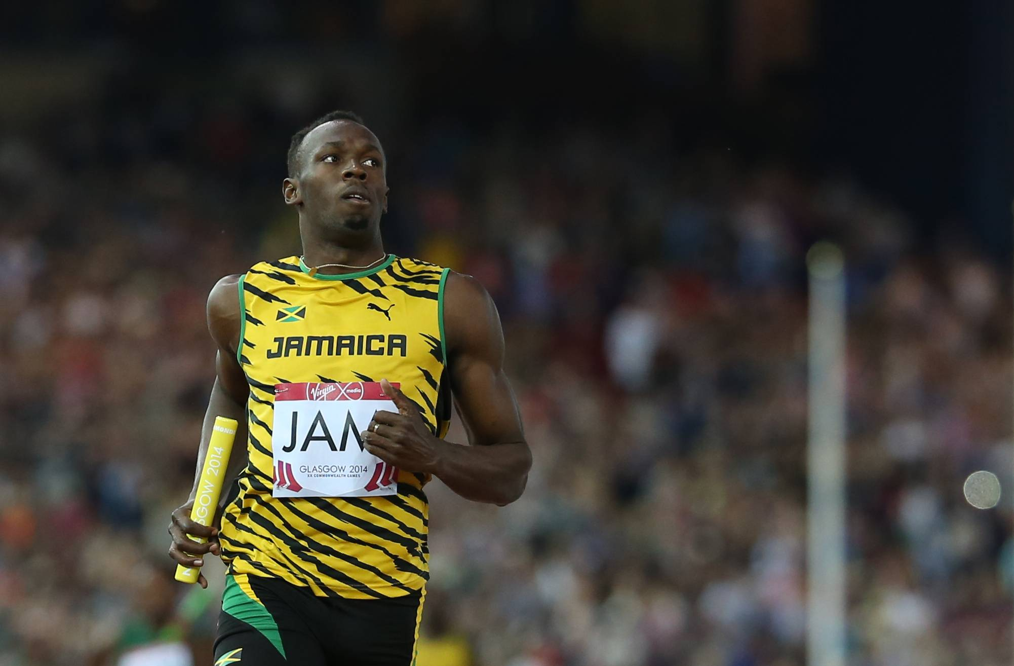 Usain Bolt of Jamaica brings the baton home as he runs the last leg of his first round heat of the men's 4 by 100 meter relay in Hampden Park stadium during the Commonwealth Games 2014 in Glasgow, Scotland, Friday Aug. 1, 2014.