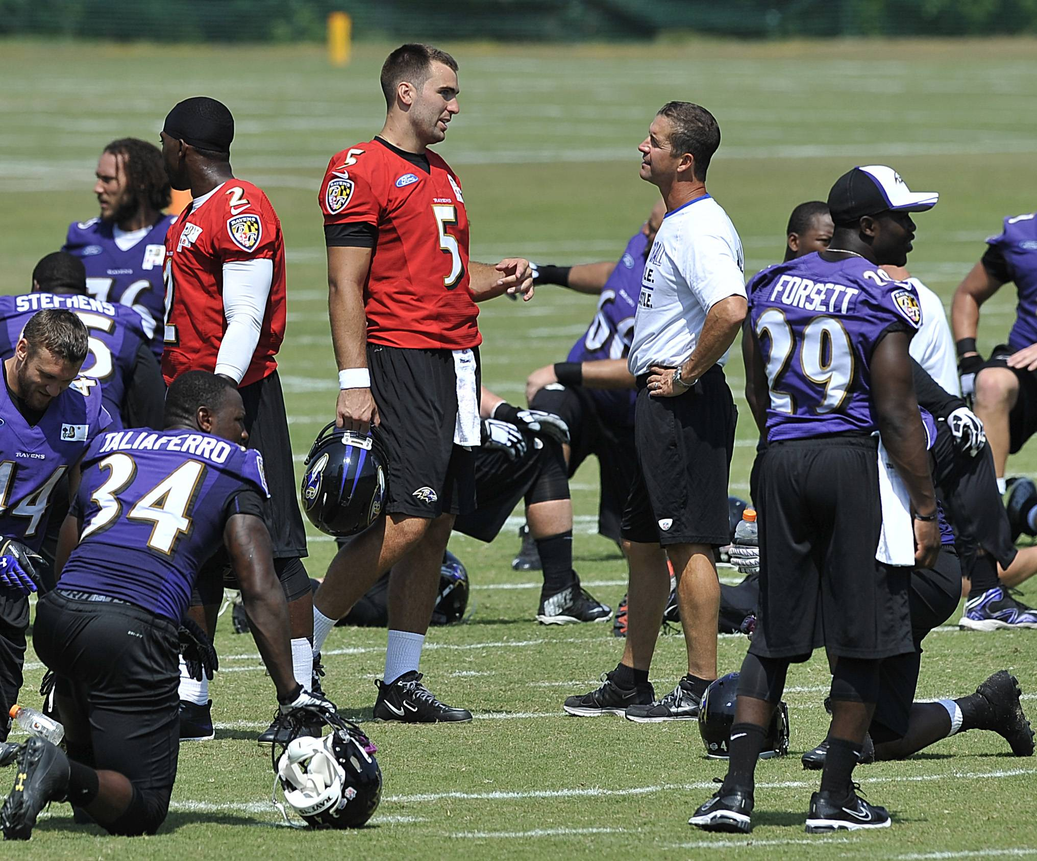 Baltimore Ravens quarterback Joe Flacco (5) talks with head coach John Harbaugh at the end of NFL football training camp practice, Thursday, July 31, 2014, in Owings Mills, Md.