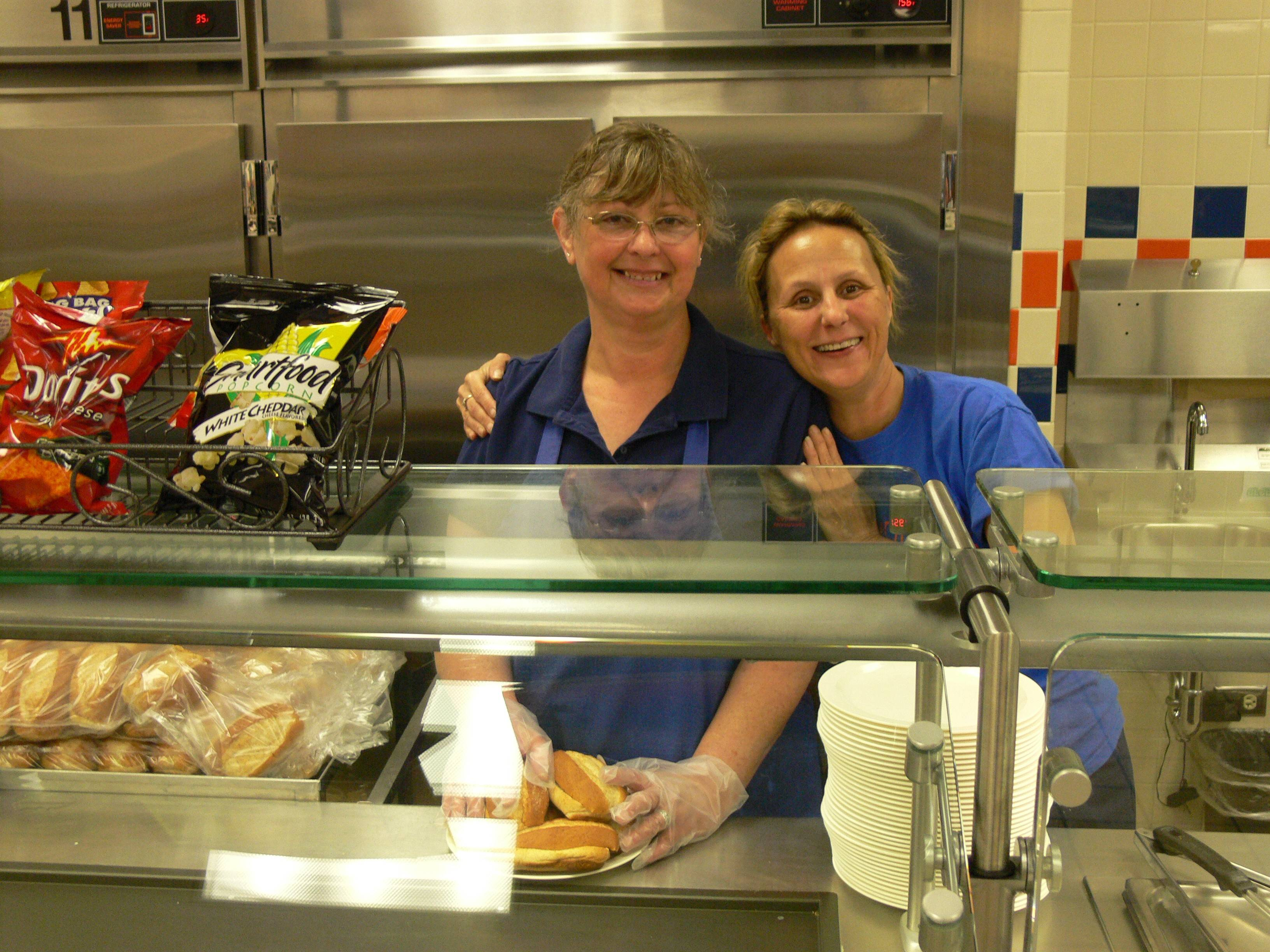 Hoffman Estates High School cafeteria workers Sue Spence, left, and Cindy O'Donnell pose for a photo.