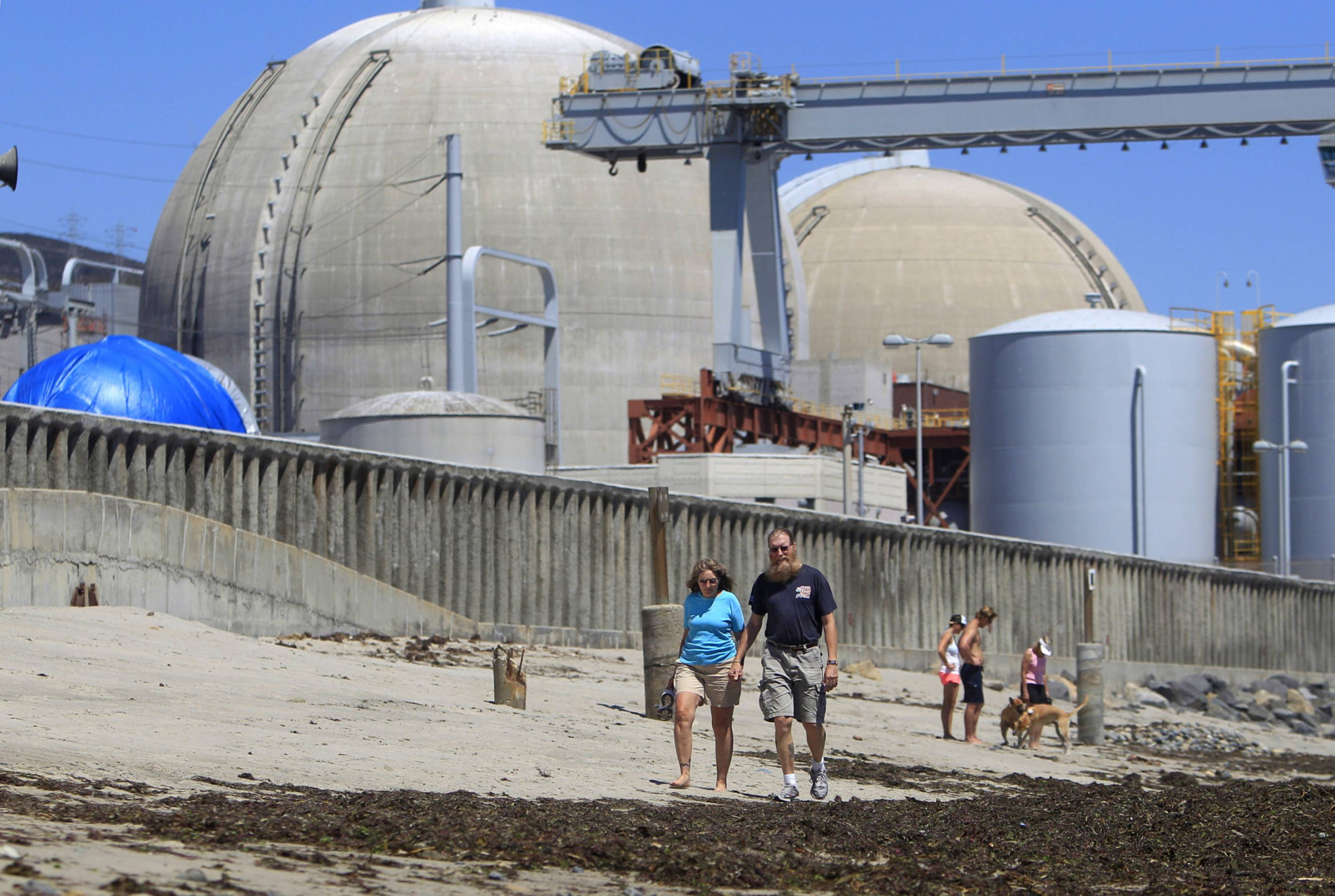 Beach-goers walking on the sand near the San Onofre nuclear power plant in San Clemente, Calif.