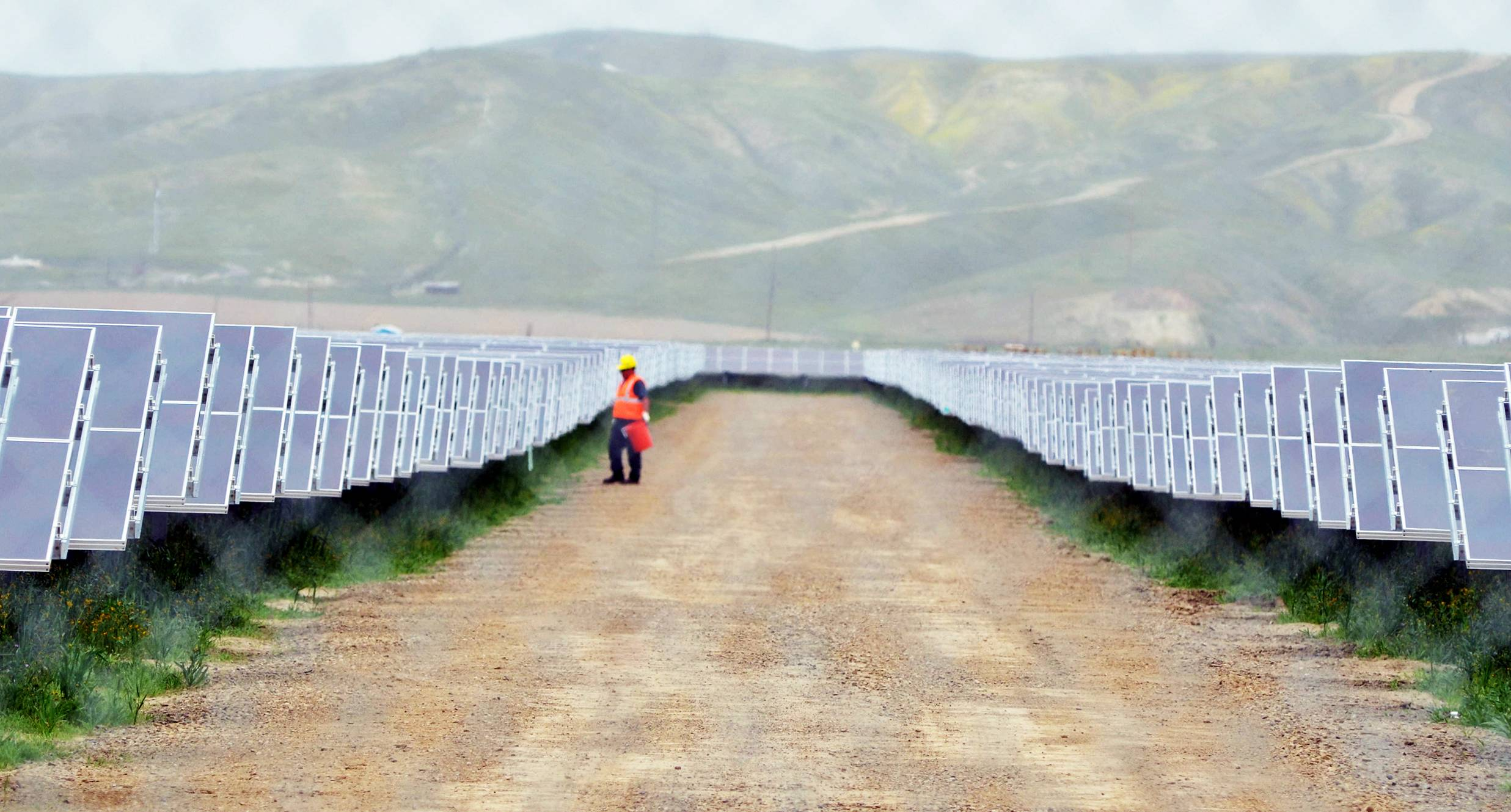 A worker looks over solar panels at the NRG Solar and Eurus Energy America Corp.'s 45-megawatt solar farm in Avenal, Calif. Energy companies are wrapping renewable energy projects and other power-related assets that generate steady cash into new companies they hope attract investors hunting for dividends.