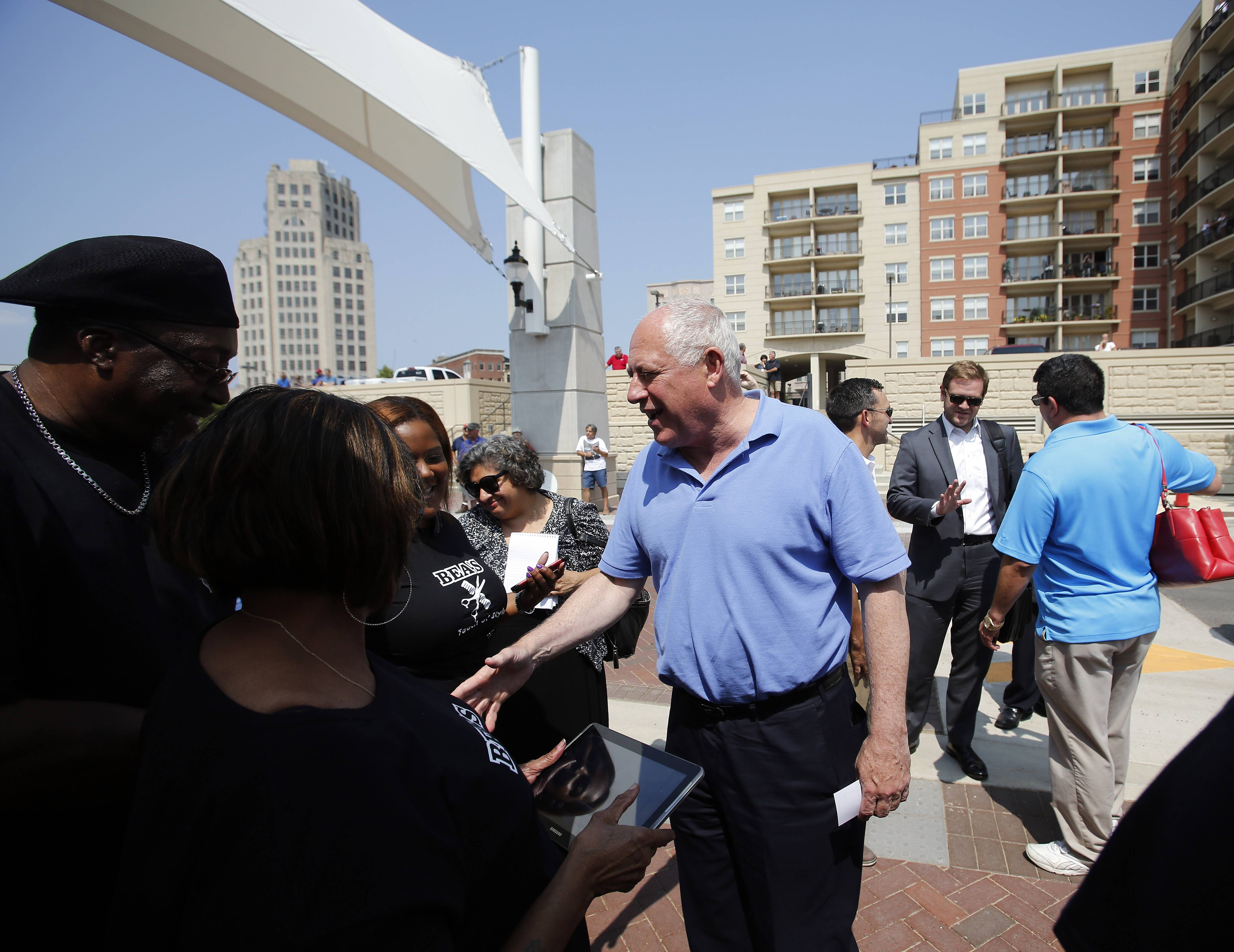 Gov. Pat Quinn greets people as he arrives Saturday for the official opening of the Riverside Drive promenade in Elgin. Work was finished in June after two years of construction using two state grants totaling $9 million.