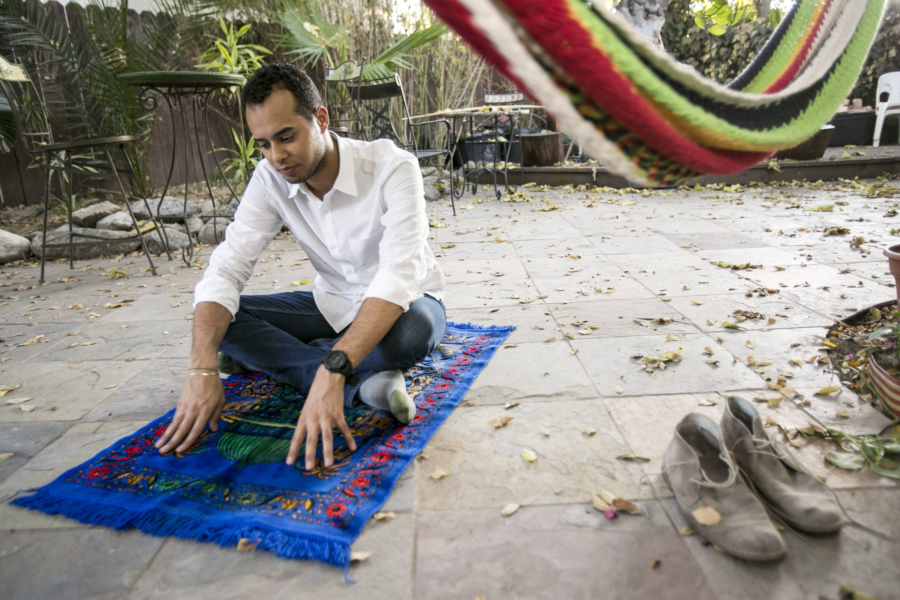 American Muslim Omar Akersim, 26, poses for a photo on his prayer rug at his home in Los Angeles Friday, Aug. 1, 2014. Nearly 40 percent of the estimated 2.75 million Muslims in the U.S. are American-born and the number is growing, with the Muslim population skewing younger than the U.S. population at large, according to a 2011 survey by the Pew Research Center.