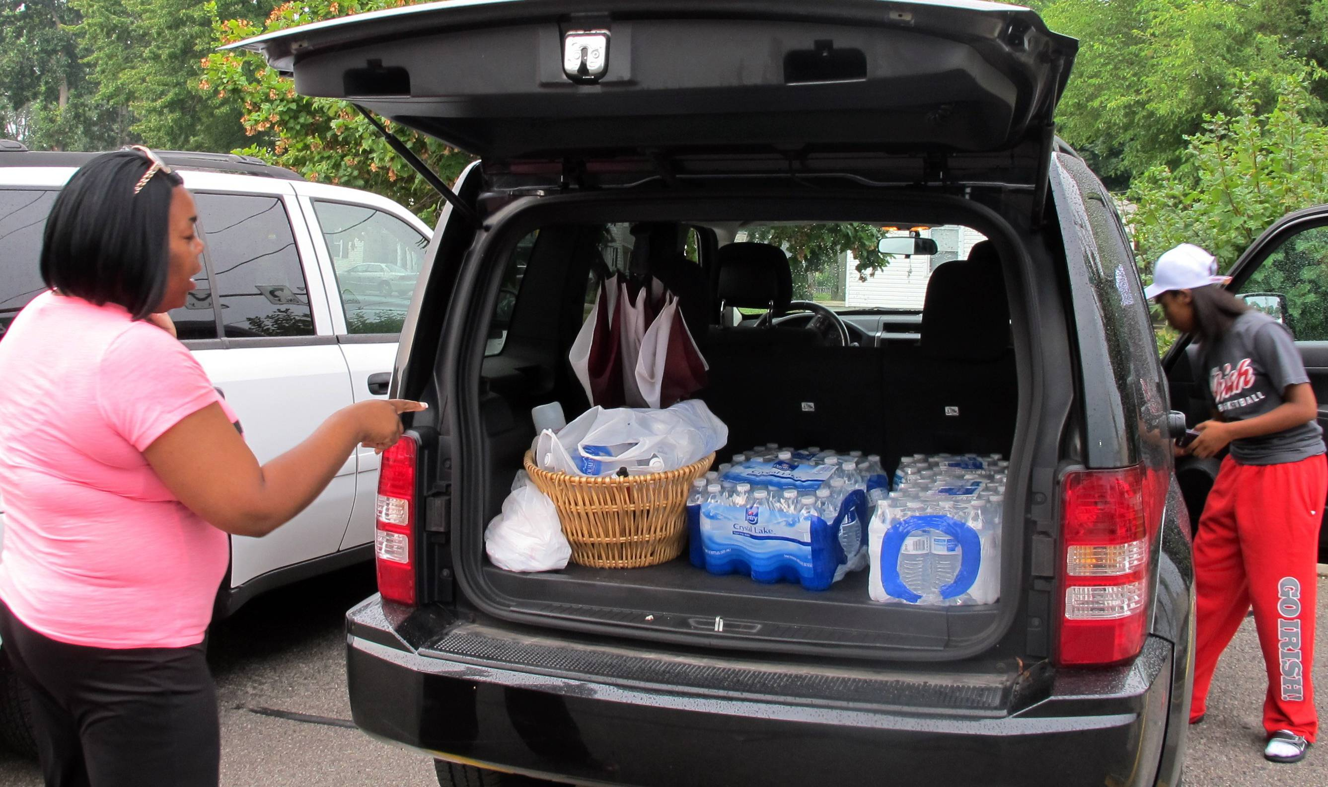 Aundrea Simmons stands next to her minivan with cases of bottled water she bought after Toledo warned residents not to use its water, Saturday, Aug. 2, 2014 in Toledo, Ohio. About 400,000 people in and around Ohio's fourth-largest city were warned not to drink or use its water after tests revealed the presence of a toxin possibly from algae on Lake Erie.