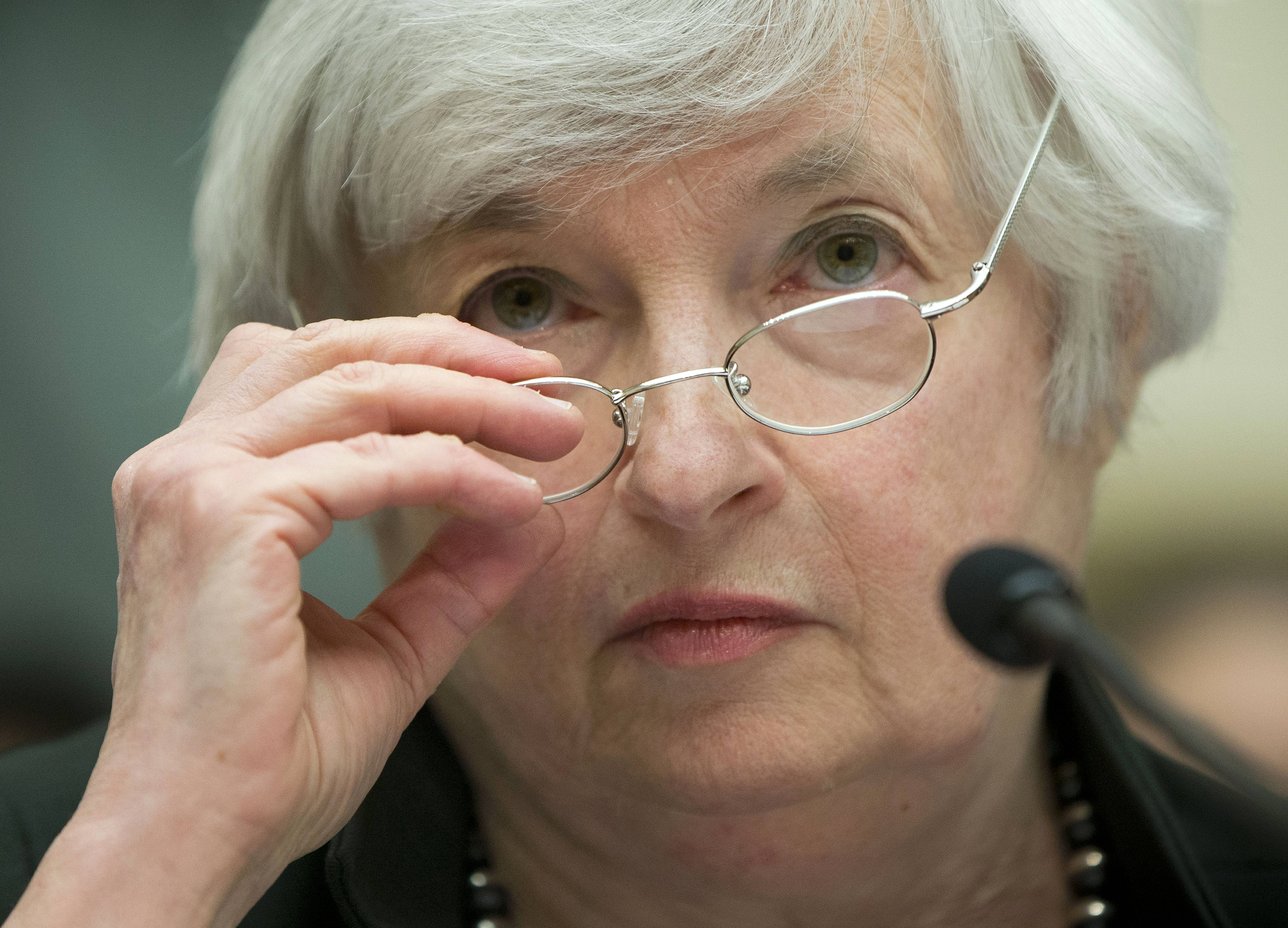 Federal Reserve Chair Janet Yellen removes her glasses as she testifies on Capitol Hill in Washington.