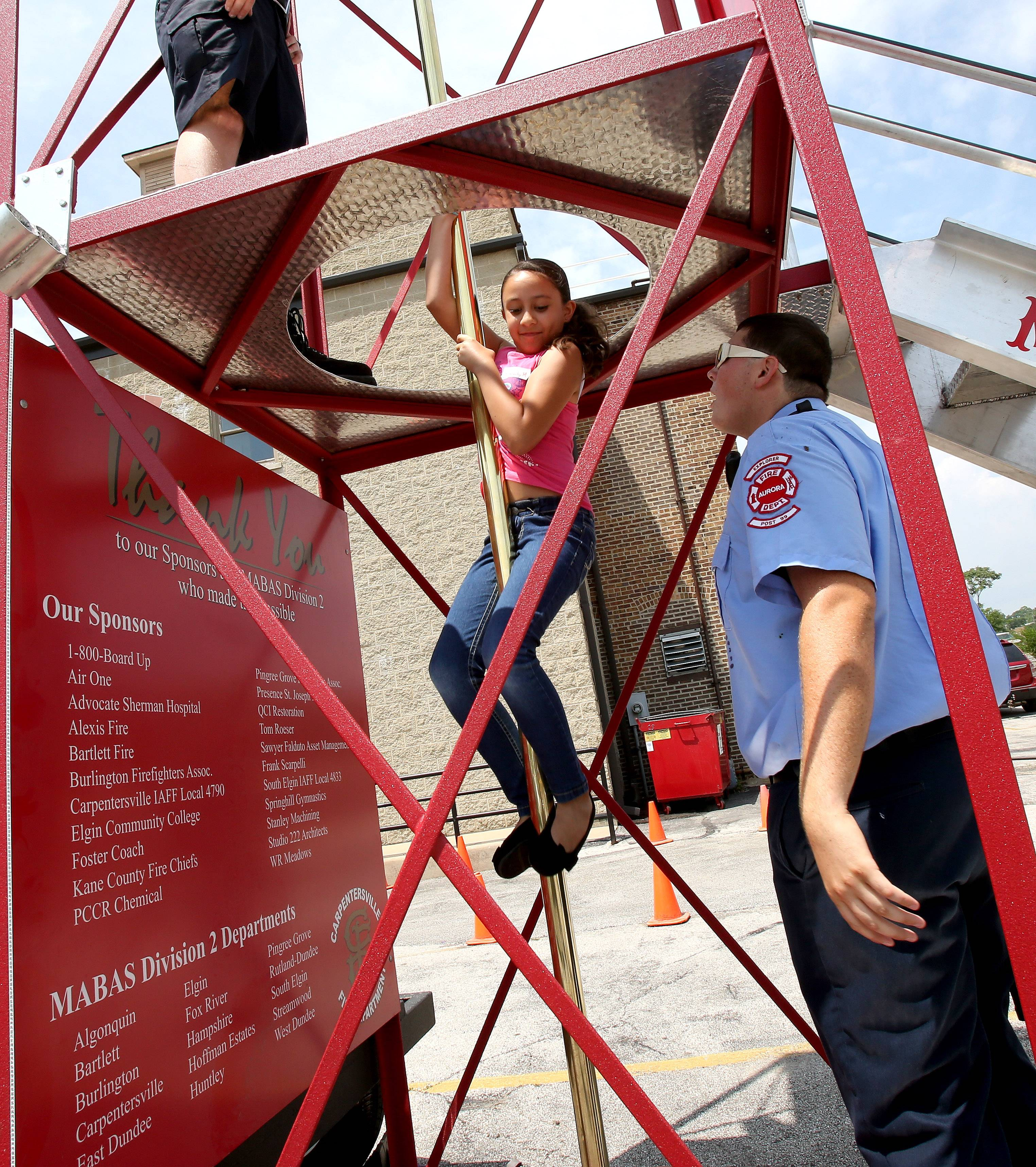 Trevor Weeks, a cadet Explorer with Aurora Post 221 and Post 99, supervises as Kimberly Menchaca, 9, makes her way down the fire pole during the Youth Firefighter Challenge summer camp at the Aurora Regional Fire Museum.