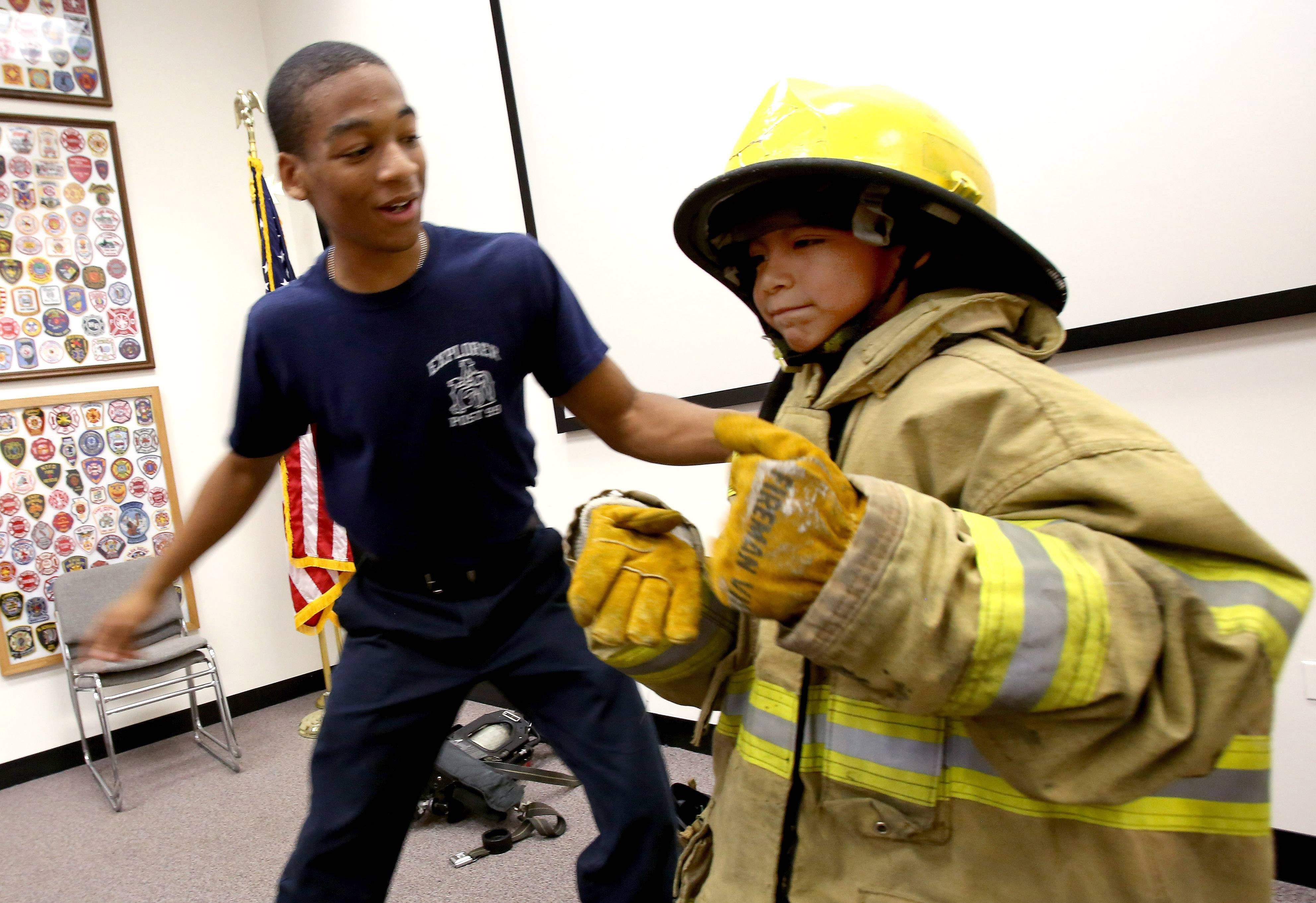 Chris Boykin, a cadet Explorer with Aurora Post 99, gets a look at 7-year-old Santiago Hernandez as he gets suited up in firefighter's gear during the Youth Firefighter Challenge summer camp.