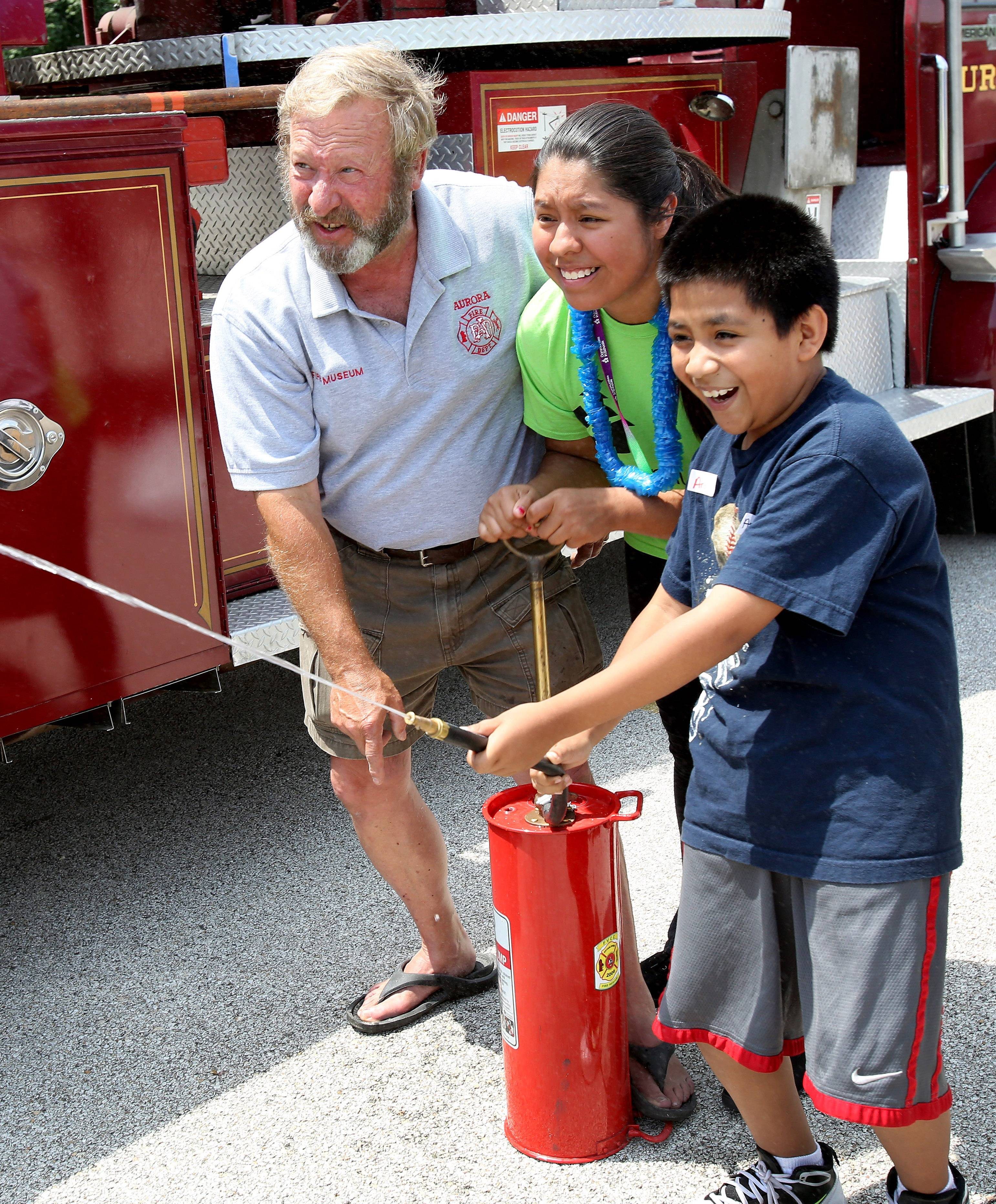 Retired Aurora firefighter, Mike Zelensek helps Evelyn Ramirez, an Aurora University student volunteer, and Andy Calderon, 10, use a pump can during the Youth Firefighter Challenge summer camp at the Aurora Regional Fire Museum.