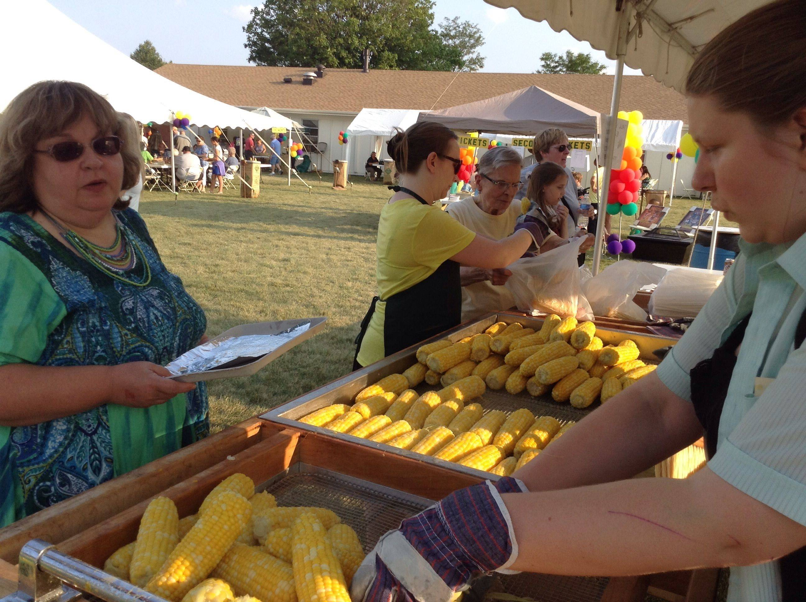 Crystal Fitzgerald, right, serves up fresh ears Saturday at the 58th annual Cornfest in Rolling Meadows.