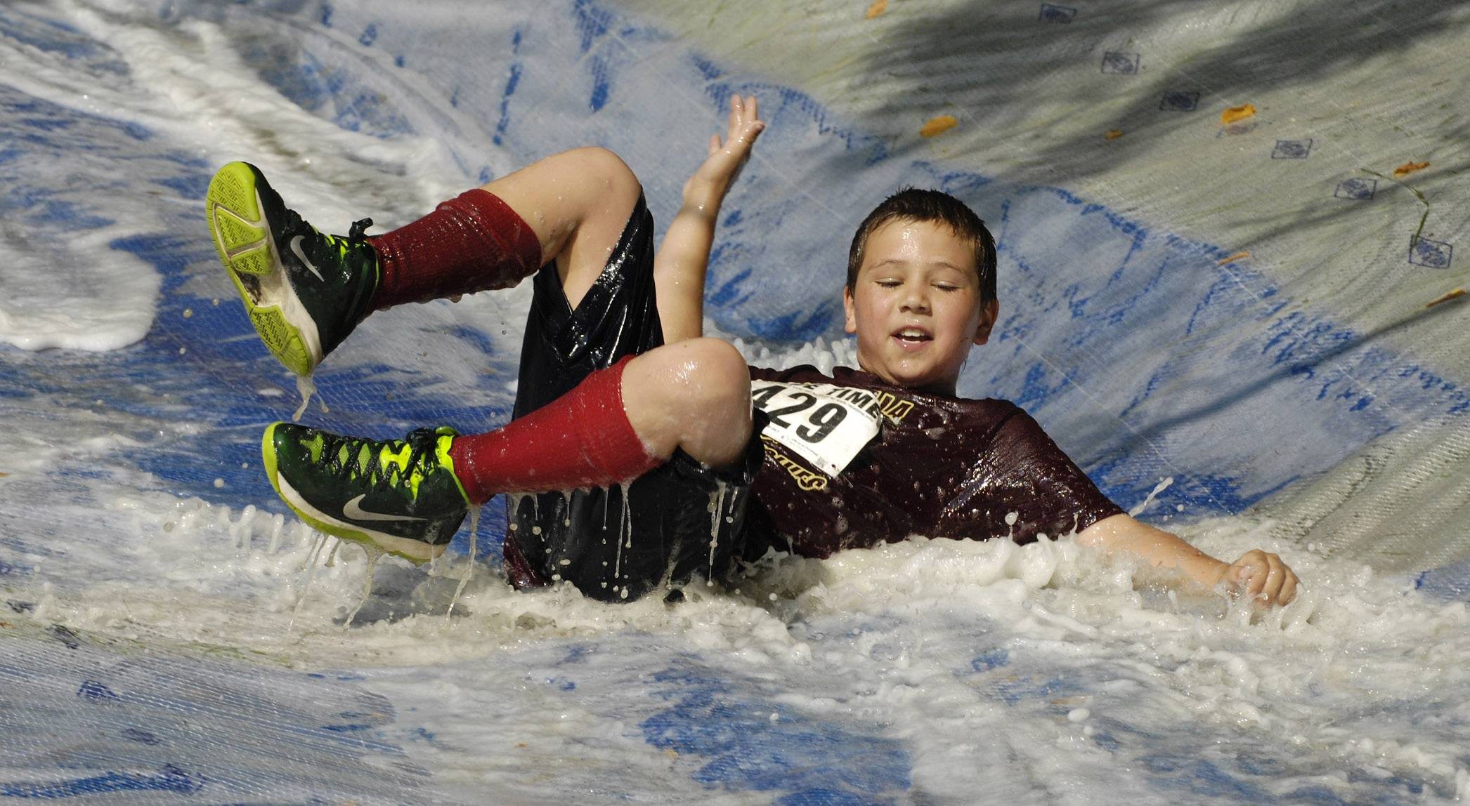 Connor Kozanecki, 10, of Lindenhurst goes down the water slide near the finish of Saturday's Mud Run at Caboose Park in Lake Villa.