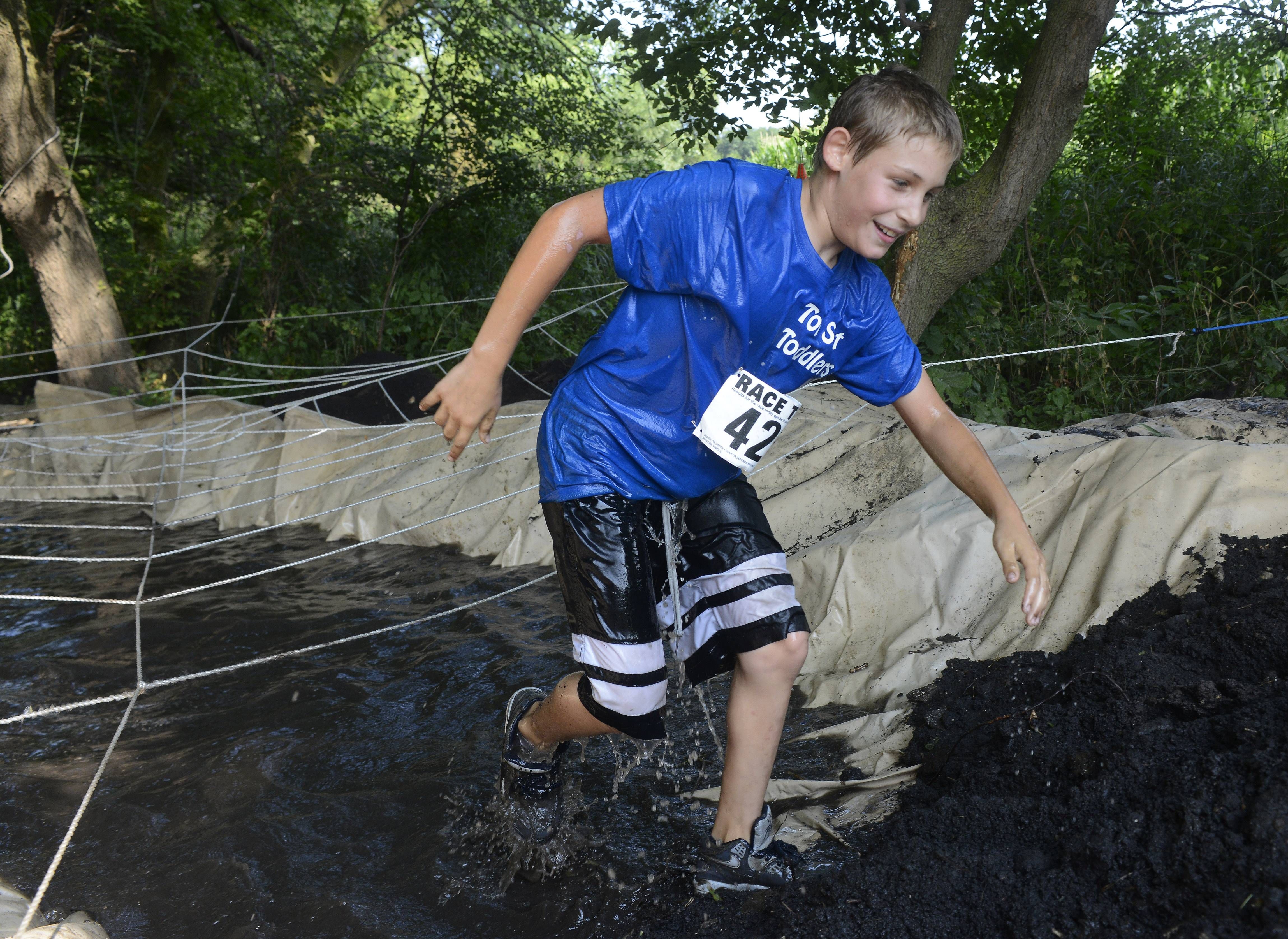 "Lee Simone, 10, of Lake Villa exits the ""spider web"" obstacle during Saturday's Mud Run at Caboose Park in Lake Villa."