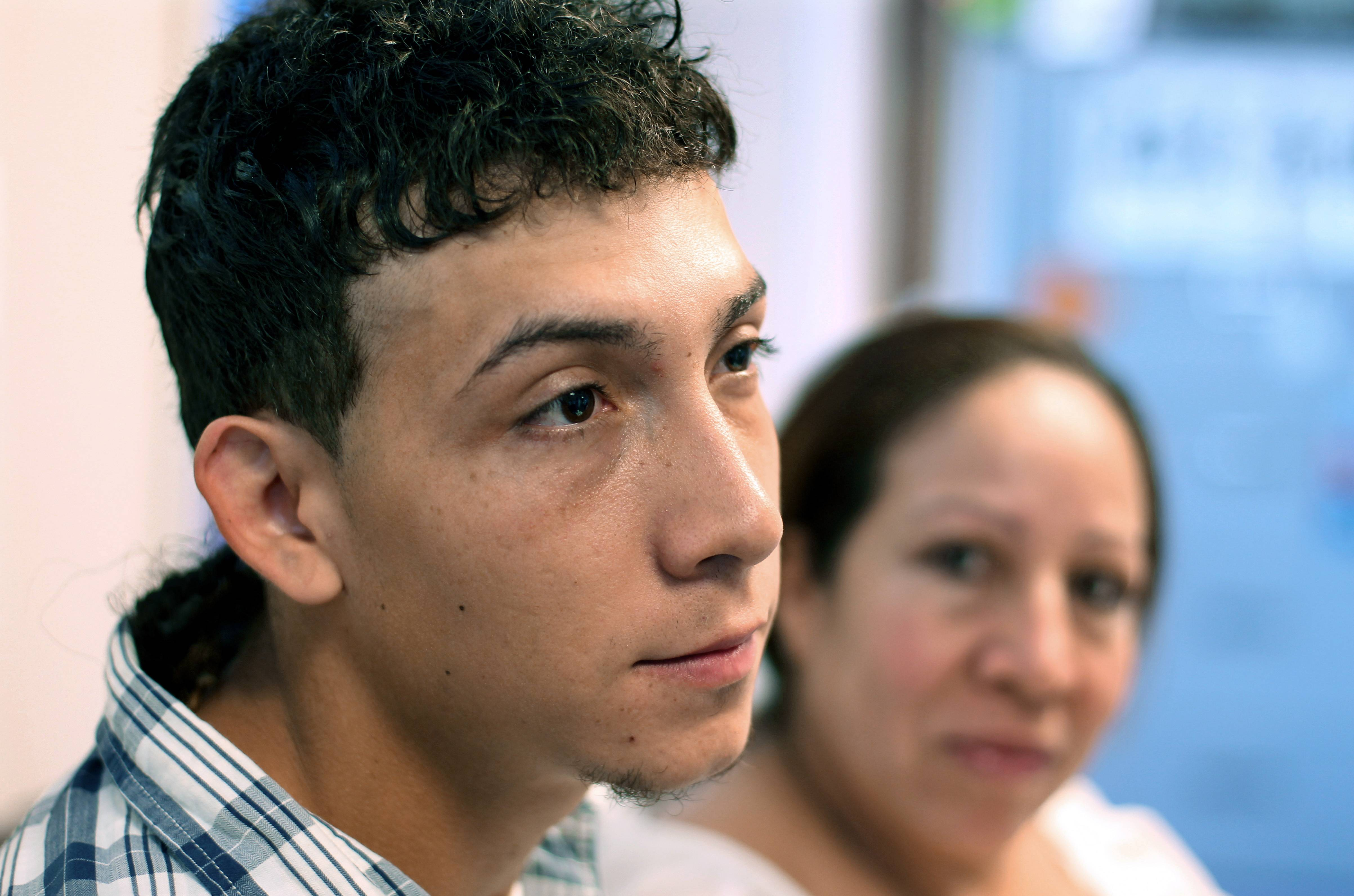 Celvyn Mejia Romero prepares to respond to a question last Sunday during an interview as his mother Susana Romero looks on at the Greater Boston Lega