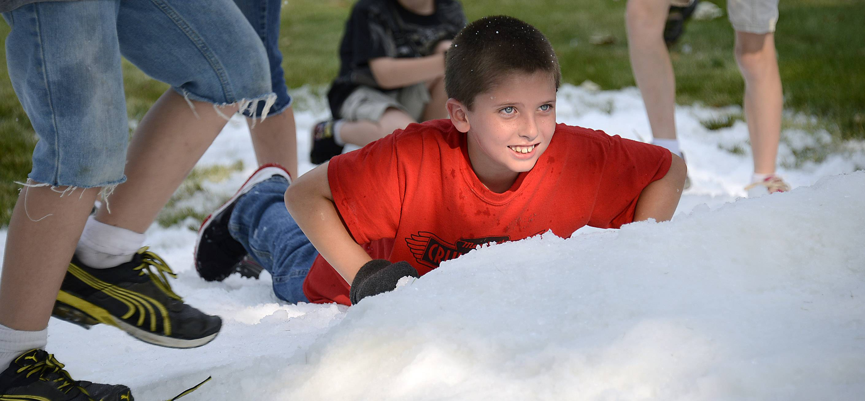 "Seth Hildebrant, 8, of Palatine plays in the snow Friday night before the outdoor showing of the movie ""Frozen"" at Meadows Christian Fellowship Church in Rolling Meadows"