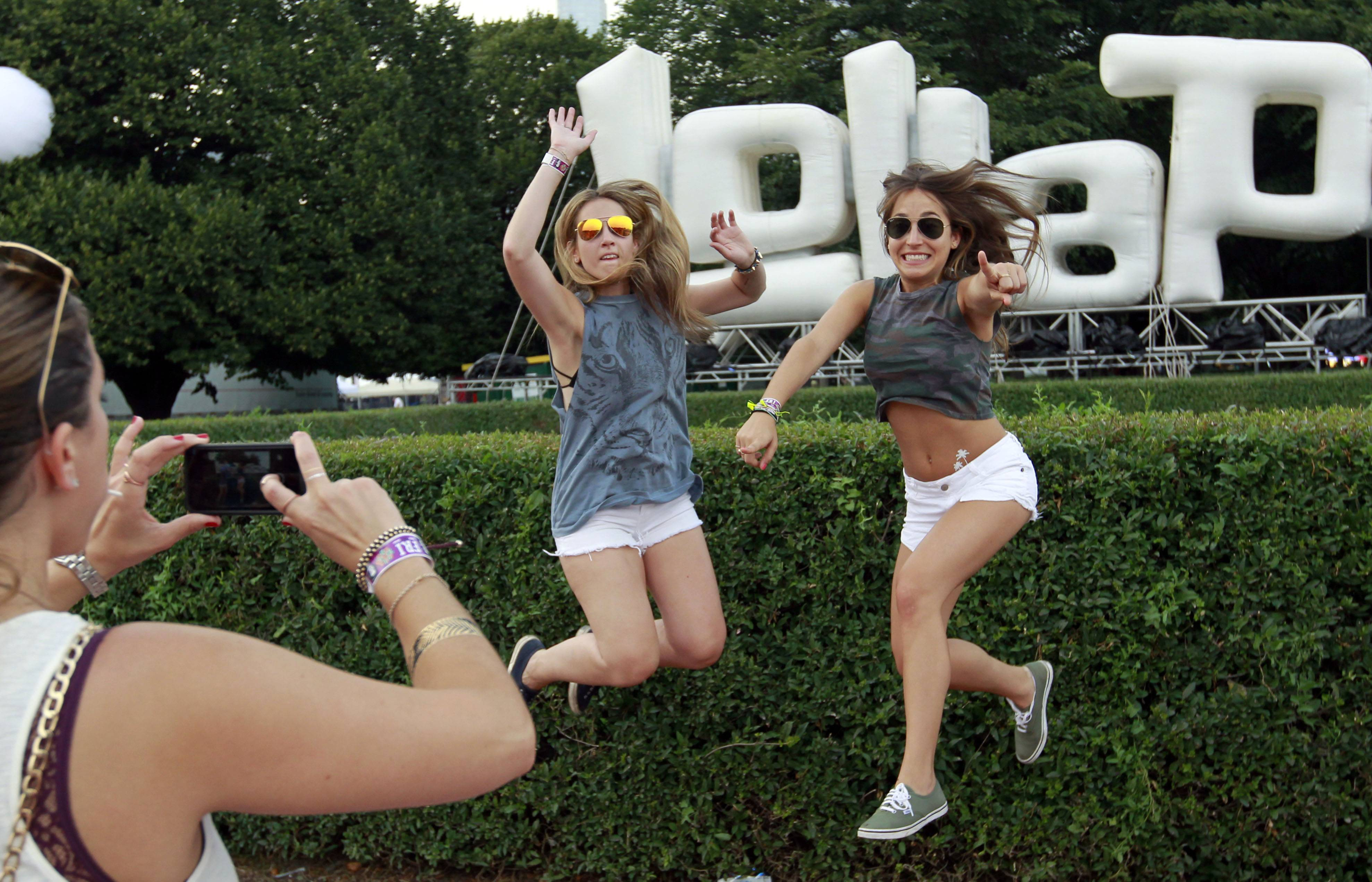 Fans pose for photos during Lollapalooza on Friday in Chicago. Once the vagabond of the music festival and touring circuit, Lollapalooza marks its 10th anniversary in Chicago.