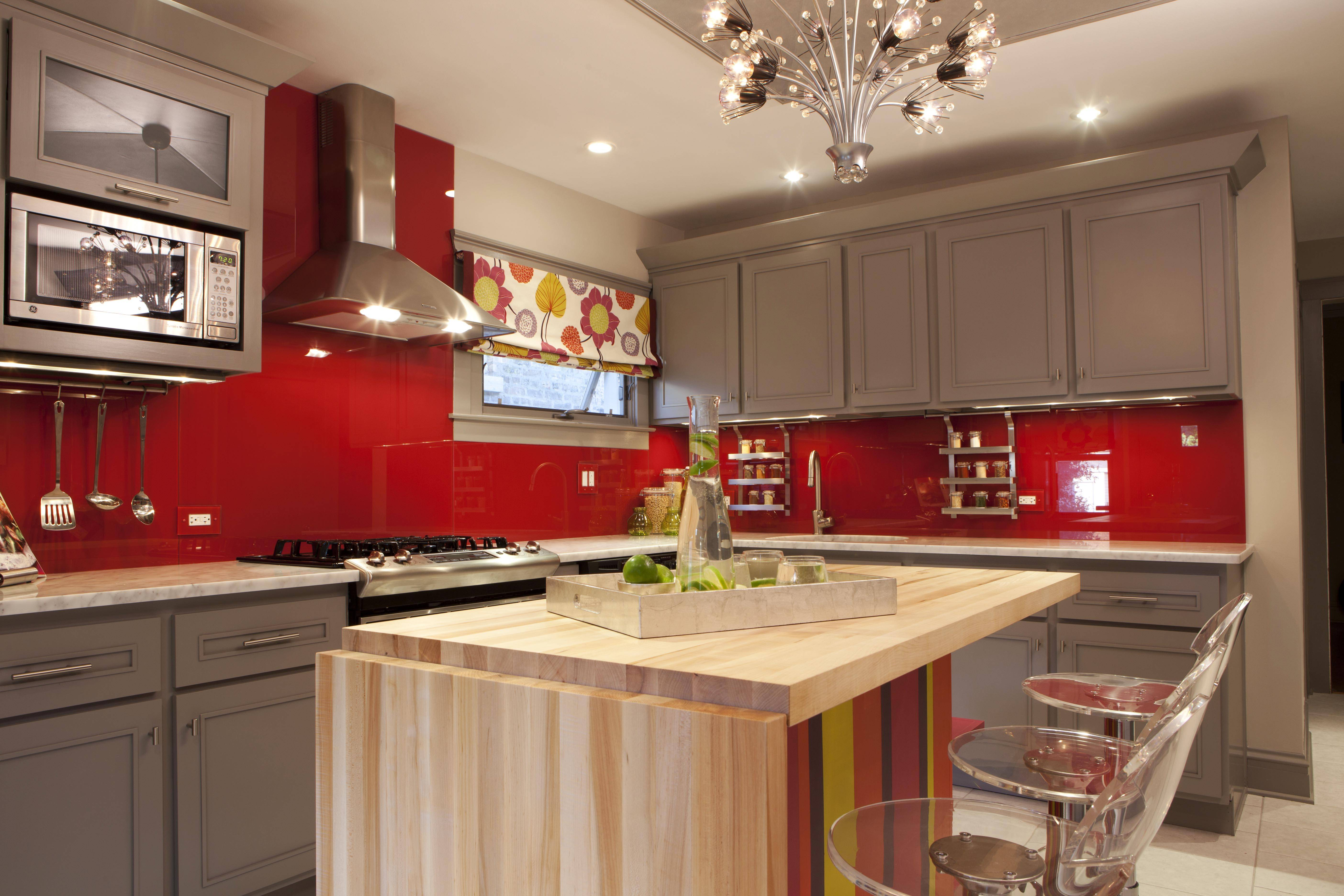 Meg Caswell, designer and host of HGTV's Great Rooms, painted the walls red then added a clear glass cover to create a chic, vibrant backsplash in this kitchen. Elements like this, as well as stools, countertop appliances and textiles are great ways to inject color into a kitchen that may have more traditional bones for a look that's unexpected and modern.