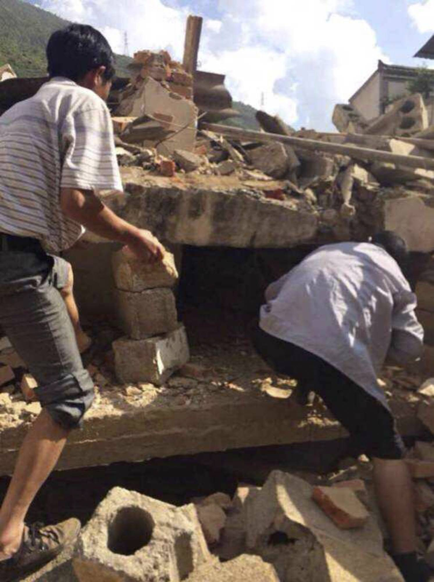 In this photo taken by cellphone and released by China's Xinhua News Agency, men at rubbles of buildings look for survivors after an earthquake Sunday in Ludian County of Zhaotong City in southwest China's Yunnan Province. A strong earthquake rattled southwest China on Sunday, knocking out communication and power lines and causing people to rush out of buildings, but there were no immediate reports of injuries.