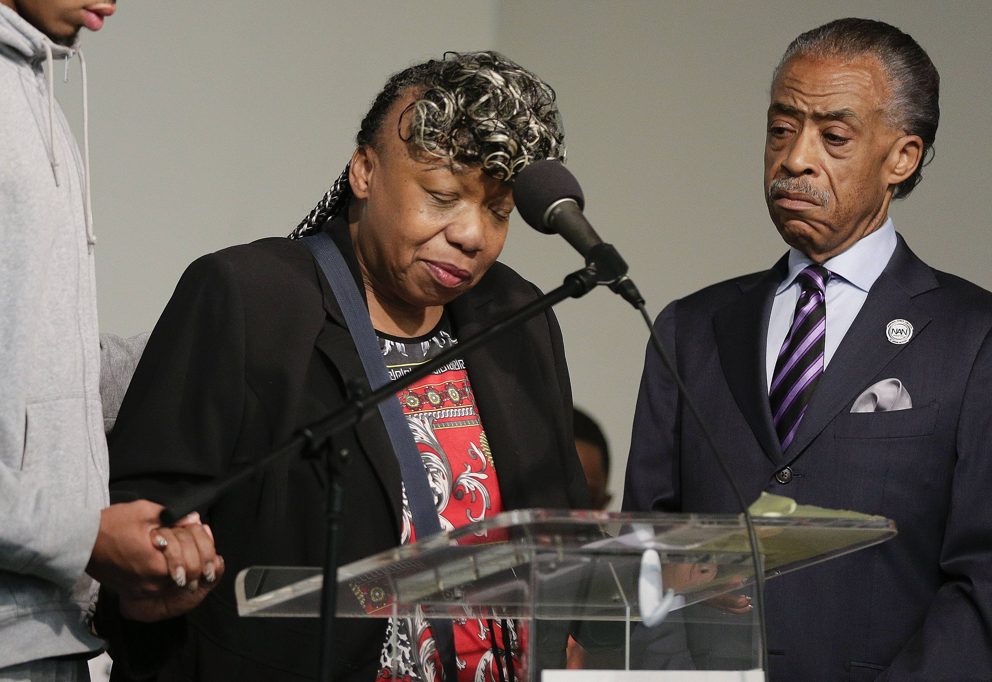 Gwen Carr, left, mother of Eric Garner, speaks Saturday as Rev. Al Sharpton looks on during a rally in New York. The rally was held to address the medical examiner's report that came Friday saying Garner's death was caused by a chokehold, a banned police maneuver.