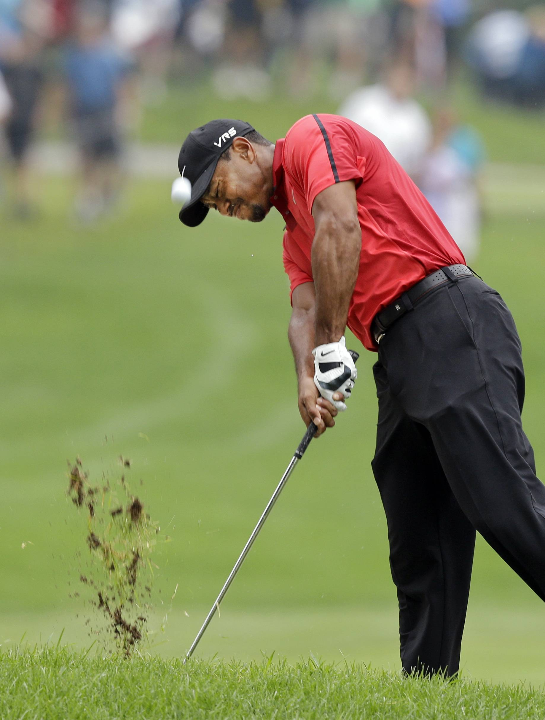 Tiger Woods hits from the lip of a fairway trap on the second hole during the final round of the Bridgestone Invitational golf tournament Sunday at Firestone Country Club in Akron, Ohio. Woods withdrew from the tournament after eight holes due to back pain.
