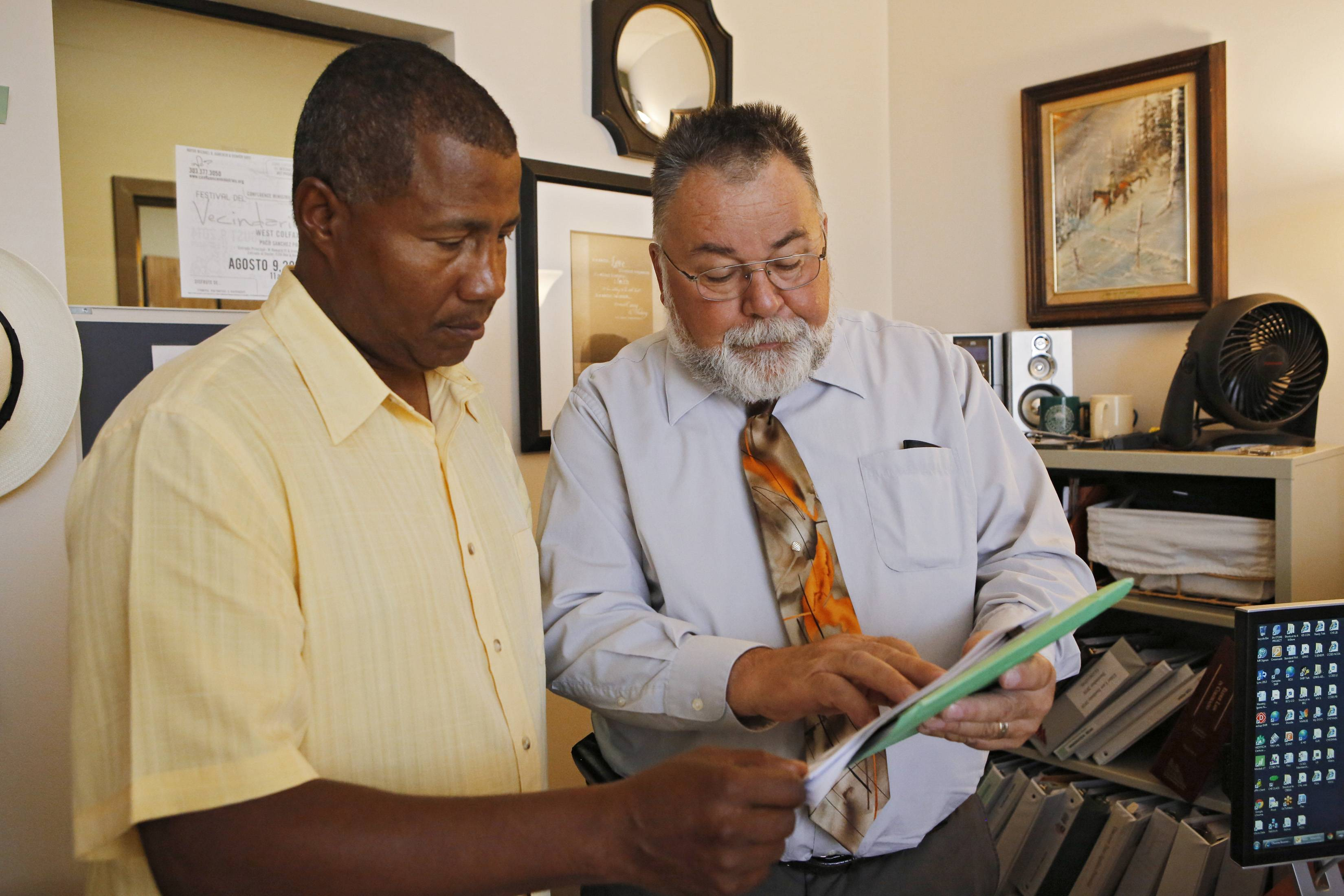 "In this July 8 photo, William Kistler, right, goes over a clients' information with support specialist Ronald Smith at Kistler's office in Denver. Sixty-three-year-old Kistler views retirement like someone tied to the tracks watching a train coming: It's looming, it's threatening and there's little he can do.""There is not enough to retire with,"" said Kistler, a Golden, Colorado, resident who said he is unable to build up a nest egg for his wife with his modest salary helping seniors navigate benefits. ""It's completely frightening to tell you the truth. And I, like a lot of people, try not to think about it too much, which is actually a problem."""