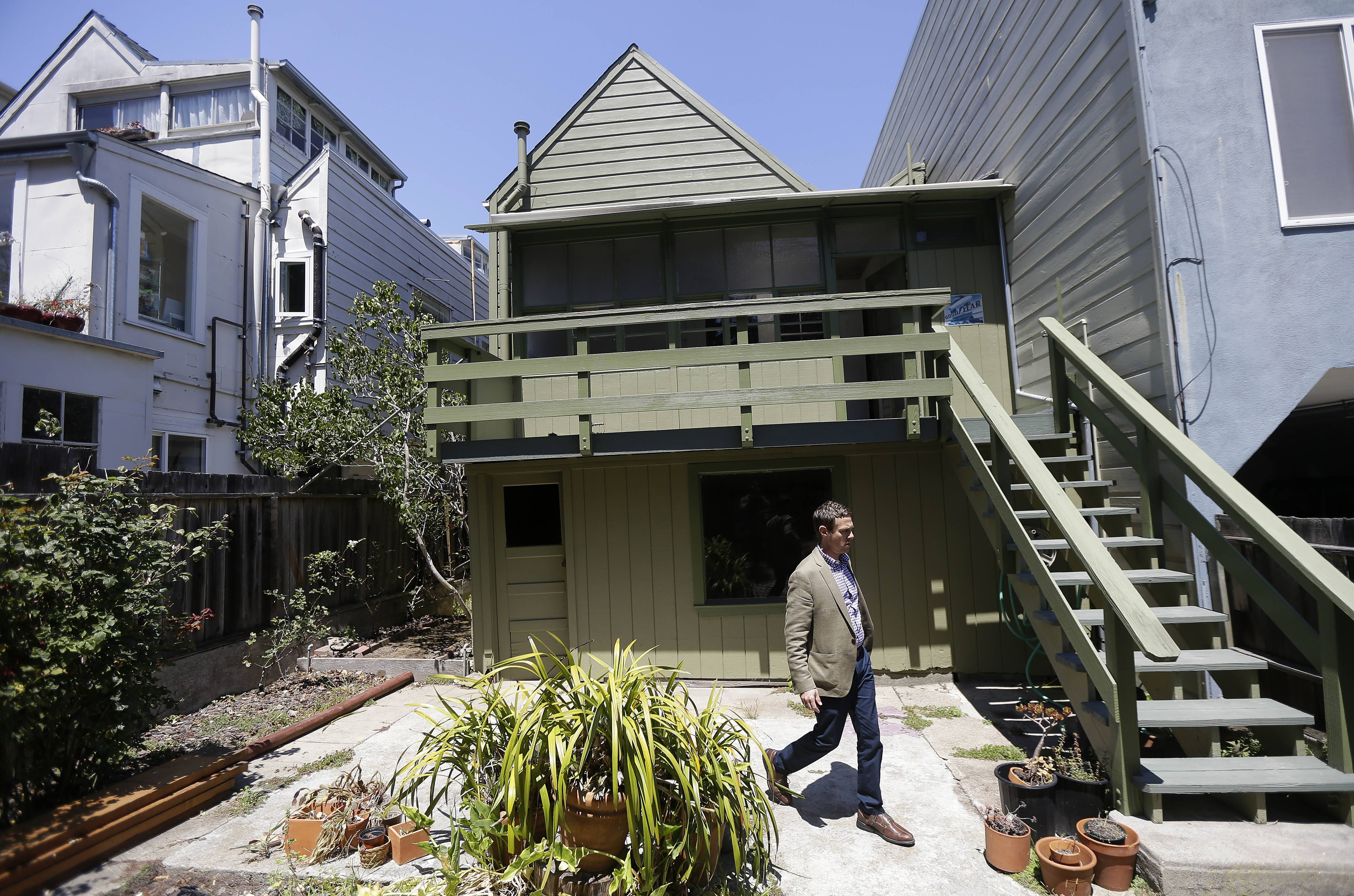 George Limperis, a realtor with Paragon Real Estate Group, walks in the backyard of a property in the Noe Valley neighborhood in San Francisco, Wednesday, July 30, 2014. In the souped-up world of San Francisco real estate, where the median selling price for homes and condominiums hit seven figures for the first time last month, the cool million that would fetch a mansion on a few acres elsewhere will now barely cover the cost of an 800-square foot starter home that needs work and may or may not include private parking.