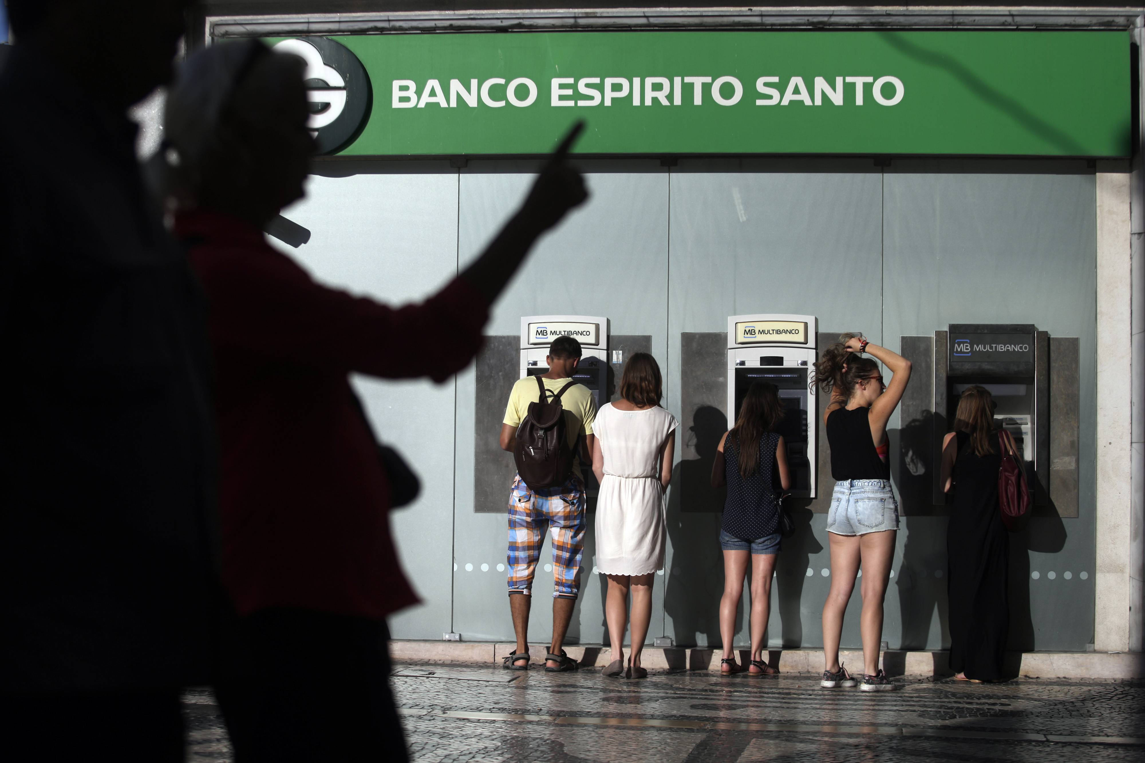 People use ATMs at a branch of Portuguese bank Banco Espirito Santo in Lisbon. The Espirito Santo family business survived wars, dictatorship, revolution and family feuds for almost 150 years. Now, one of Europe's last banking dynasties is being stripped of its wealth and influence amid accounting irregularities, huge unreported debts, and a police investigation.