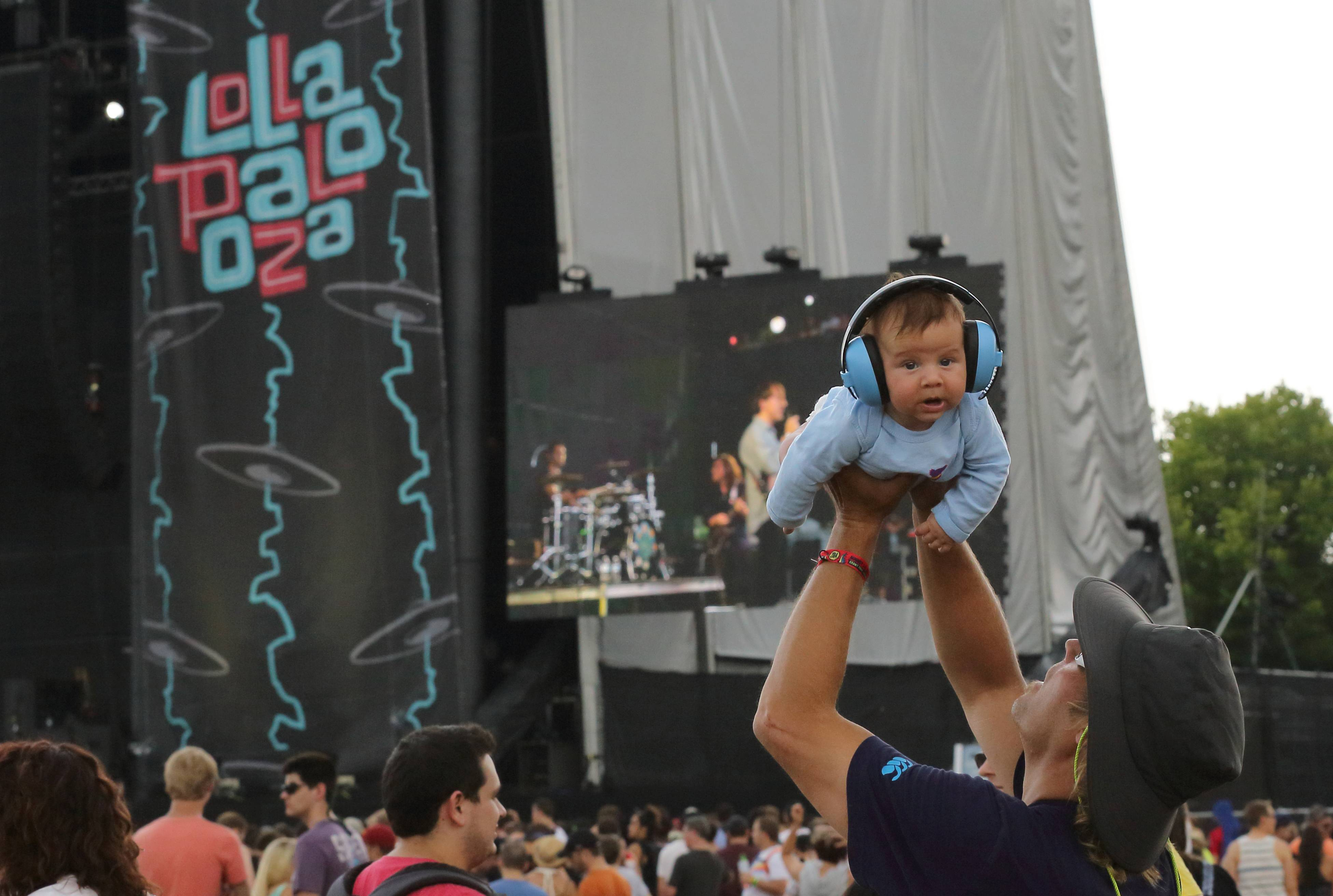 A man holds a baby wearing ear protection during a performance Firday at Lollapalooza in Chicago's Grant Park.