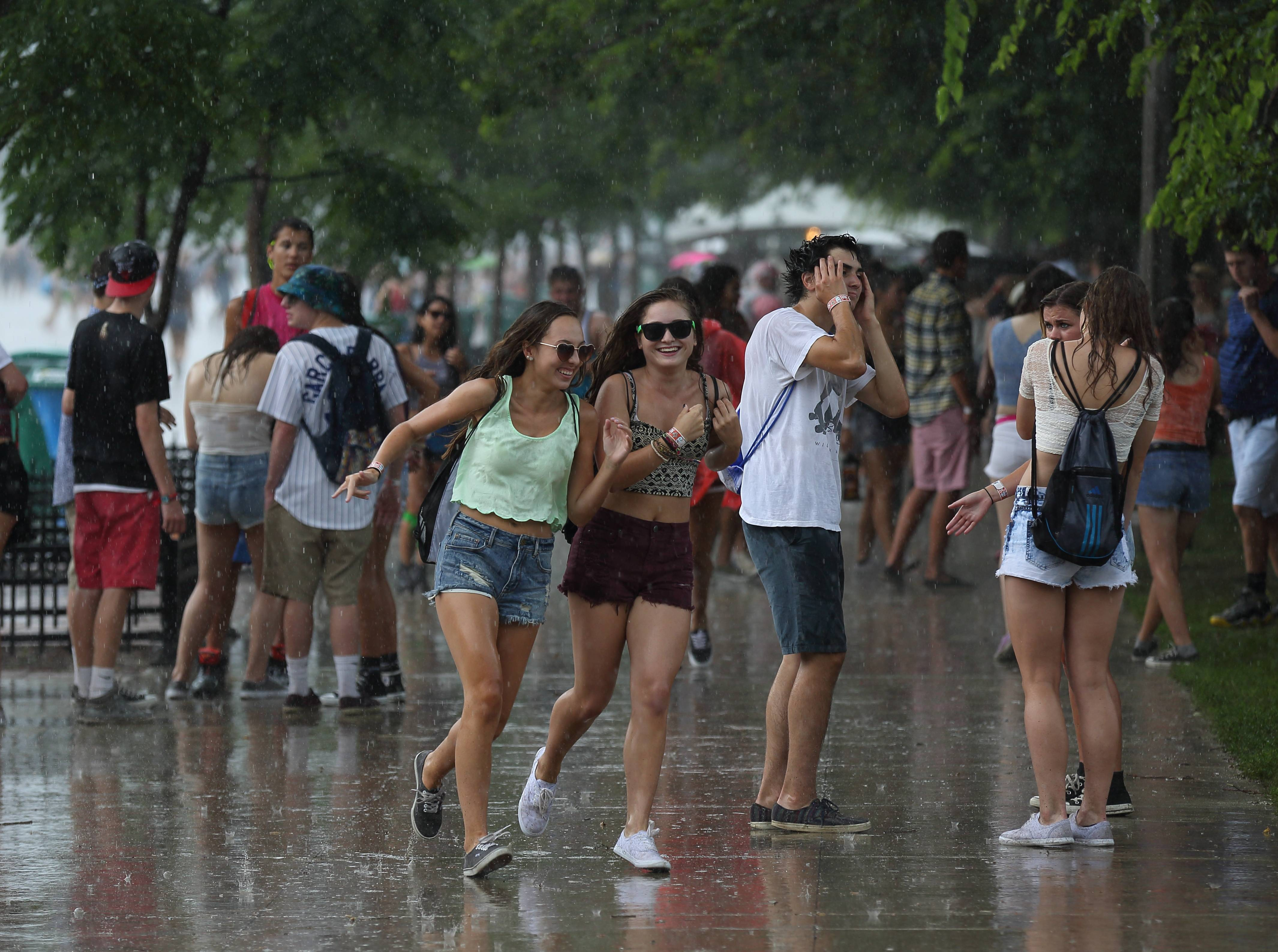 Lollapalooza attendees look for cover as rain storms roll in Sunday at the Lollapalooza Music Festival in Chicago's Grant Park.