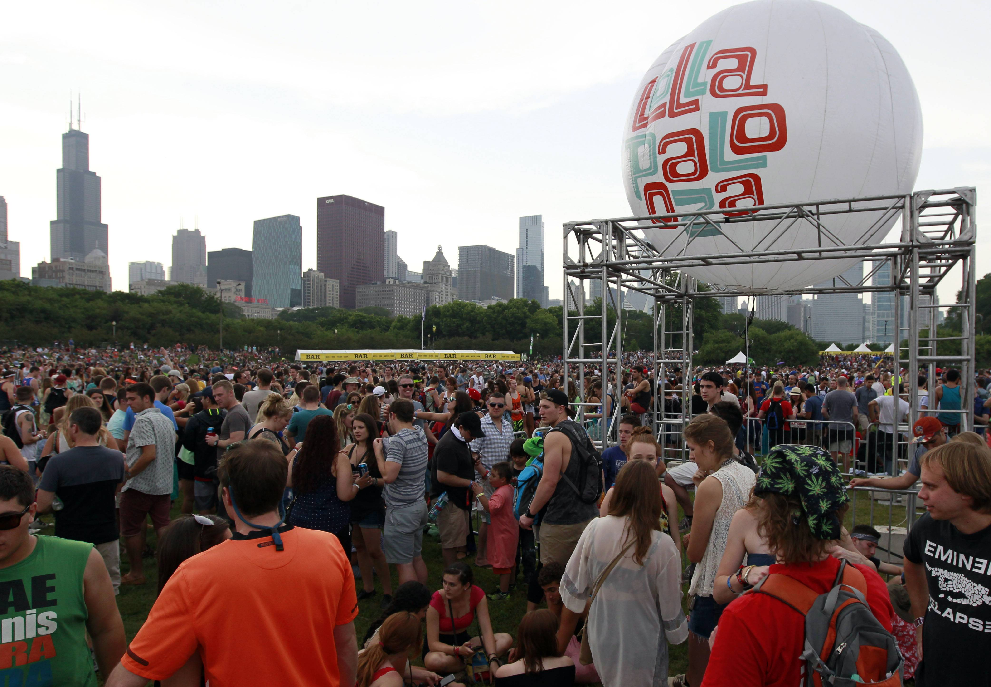 People wait for the band Chvrches to take the stage Friday during Lollapalooza. Once the vagabond of the music festival and touring circuit, Lollapalooza marks its 10th anniversary in Chicago.