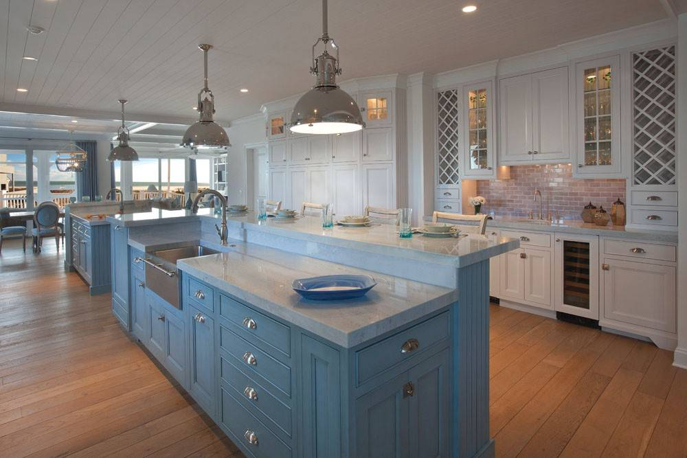 Warm up the kitchen by combining cabinets with different finishes and modern chandeliers in a transitional kitchen.