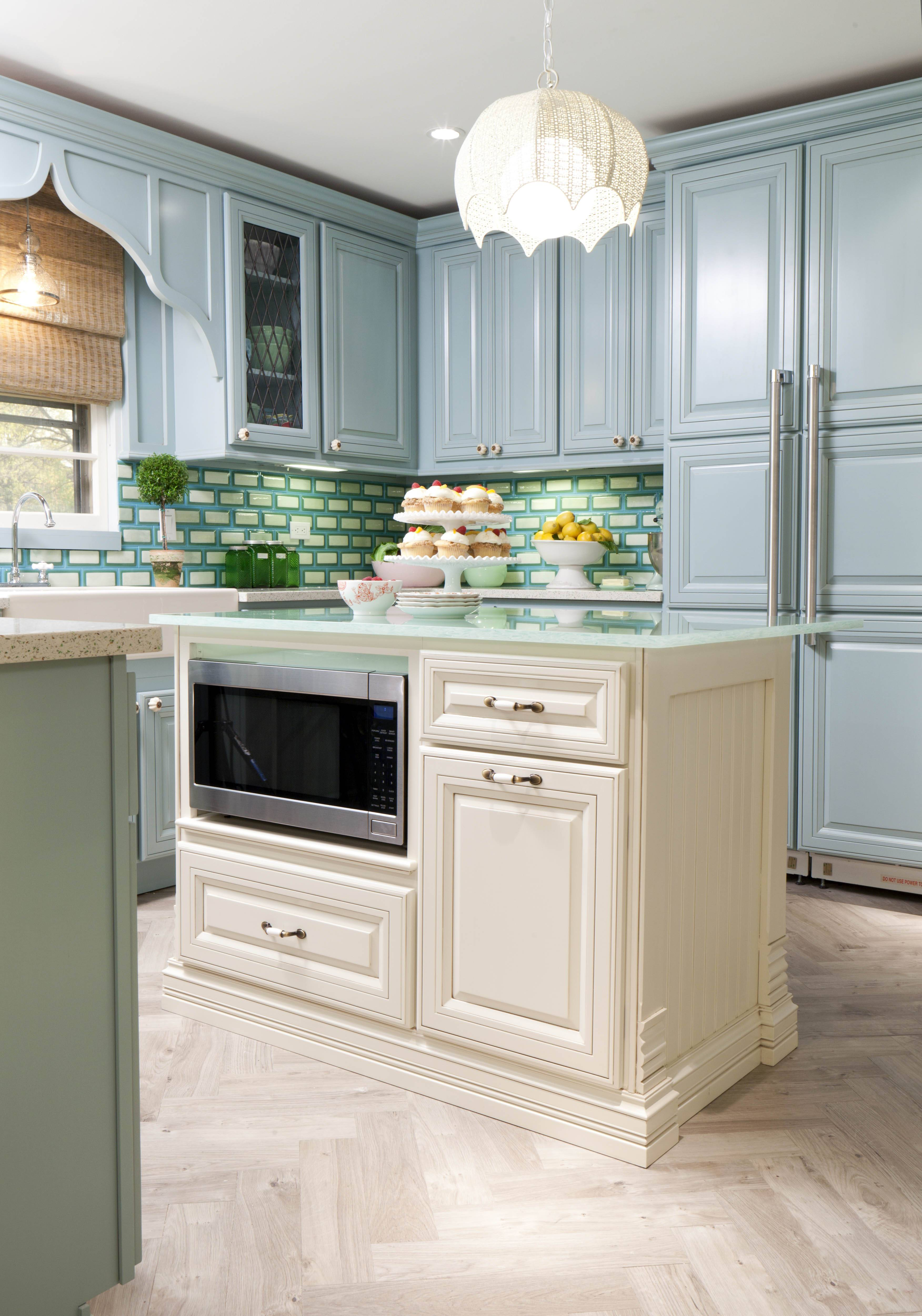Caswell used crisp, colorful blue green and white fused glass tiles to create a dynamic backsplash in this kitchen. The look is a good blend of contemporary and traditional.