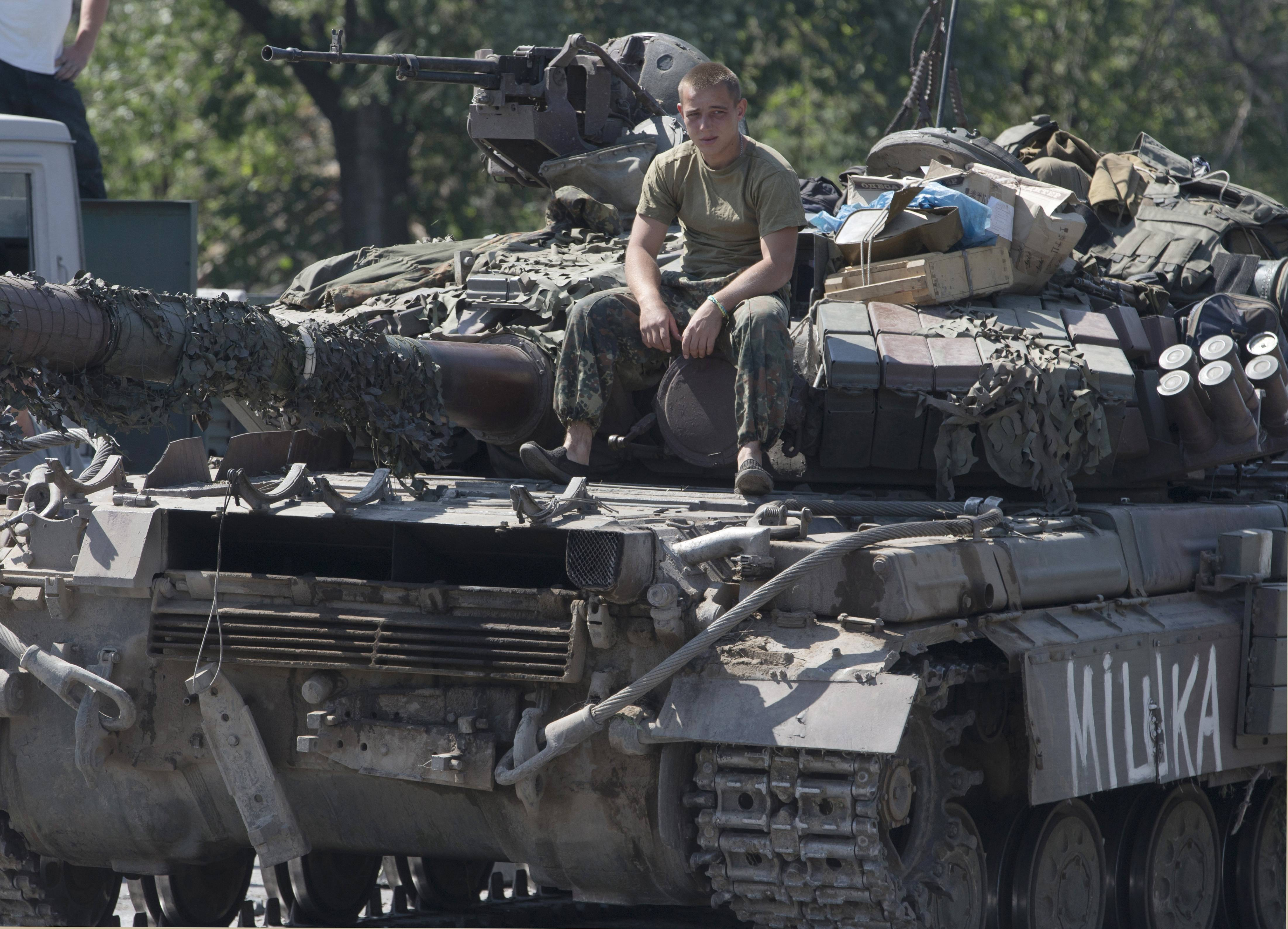 A Ukrainian government army soldier rests on his tank Friday at a block-post in the village of Debaltseve, eastern Ukraine. Fighting raged Sunday on the outskirts of Donetsk as the Ukranian Army tried to seize control of the rebel stronghold.