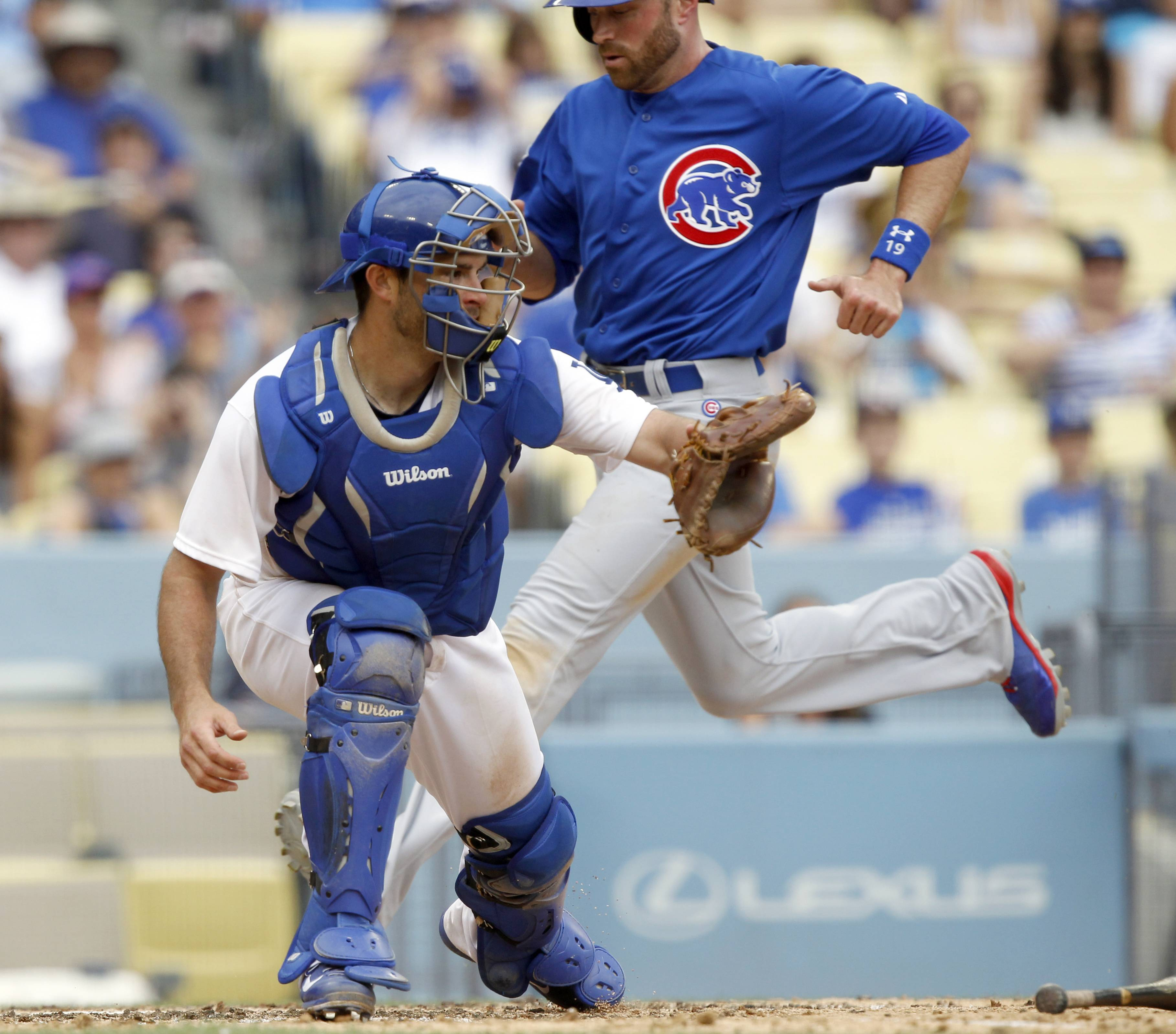 Chicago Cubs' Nate Schierholtz, right, beats the throw to Los Angeles Dodgers catcher Drew Butera, left, from center field, to score with Cubs' Chris Valaika on a single by the Cubs' Starlin Castro in the eighth inning of a baseball game on Sunday, Aug. 3, 2014, in Los Angeles.