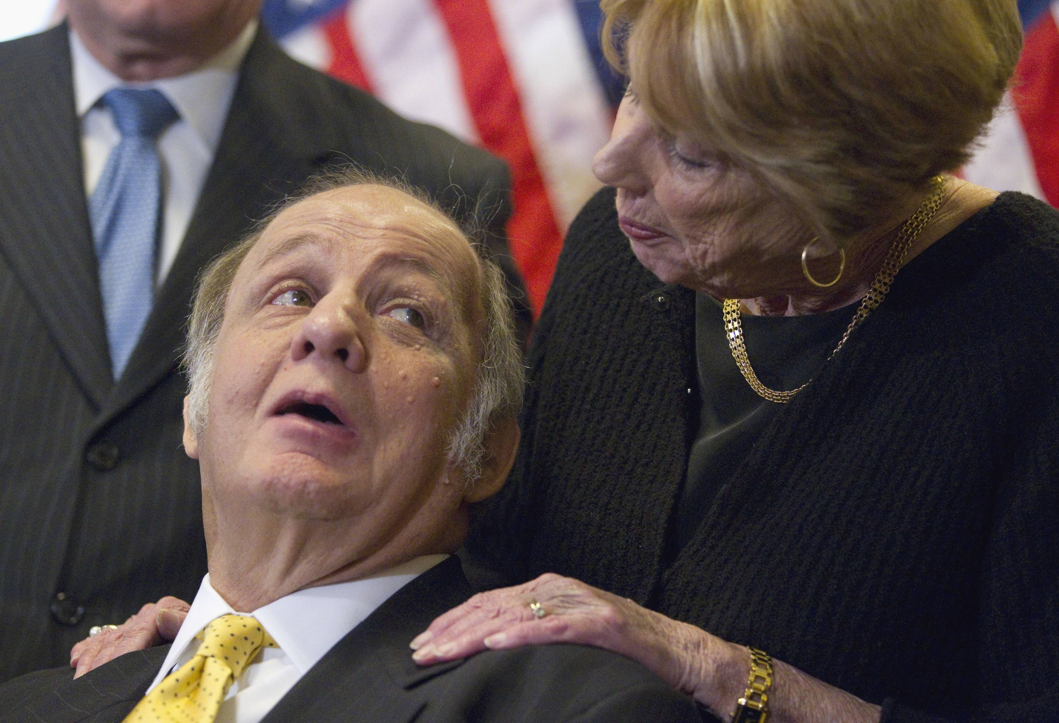 Former White House Press Secretary James Brady, who was left paralyzed in the Reagan assassination attempt, looks at his wife, Sarah, during a news conference on Capitol Hill in Washington marking the 30th anniversary of the shooting. A Brady family spokeswoman says Brady has died at 73.
