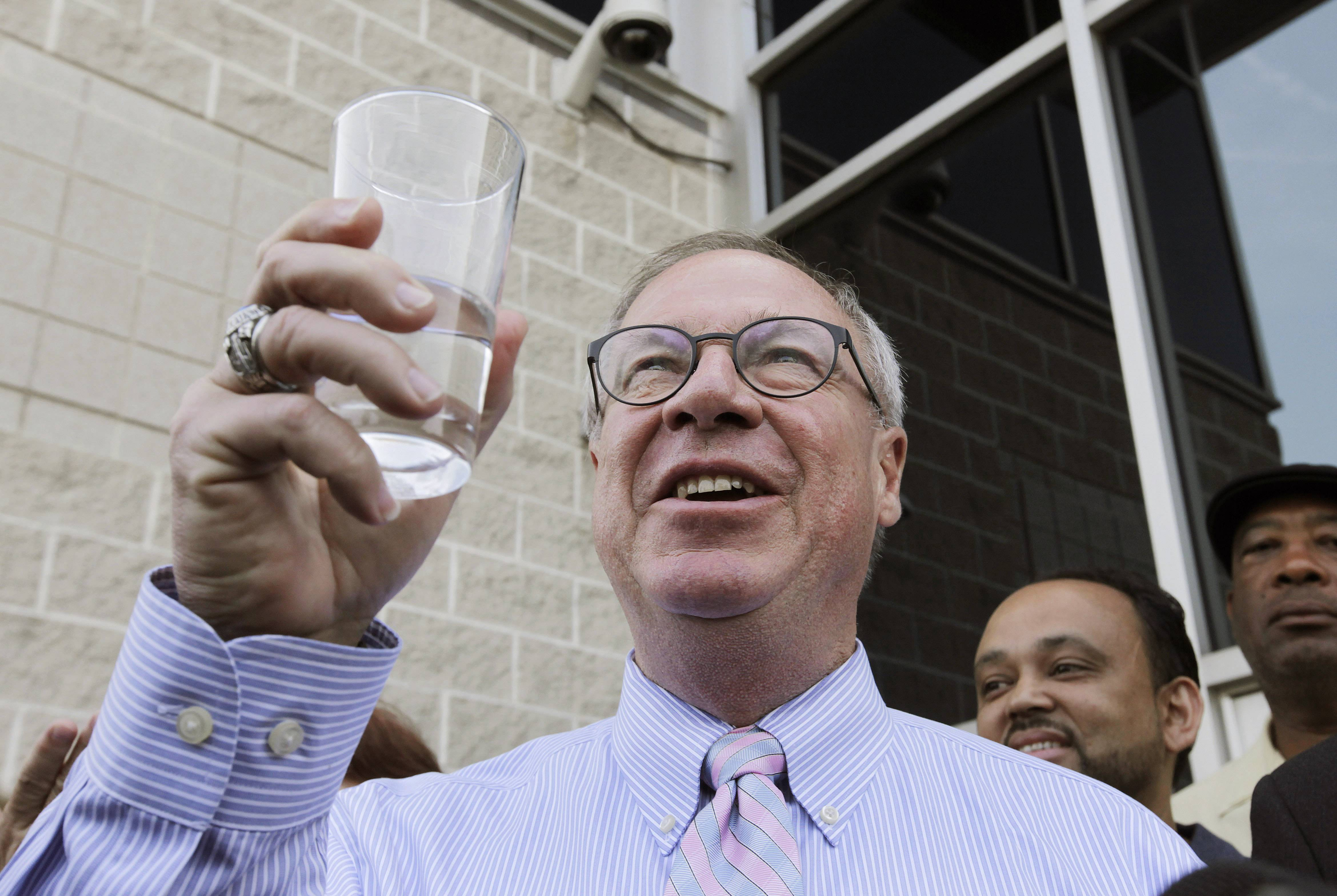Toledo Mayor D. Michael Collins raises a glass of tap water before drinking it during a news conference in Toledo, Ohio, Monday. A water ban that had hundreds of thousands of people in Ohio and Michigan scrambling for drinking water has been lifted, Collins announced Monday.