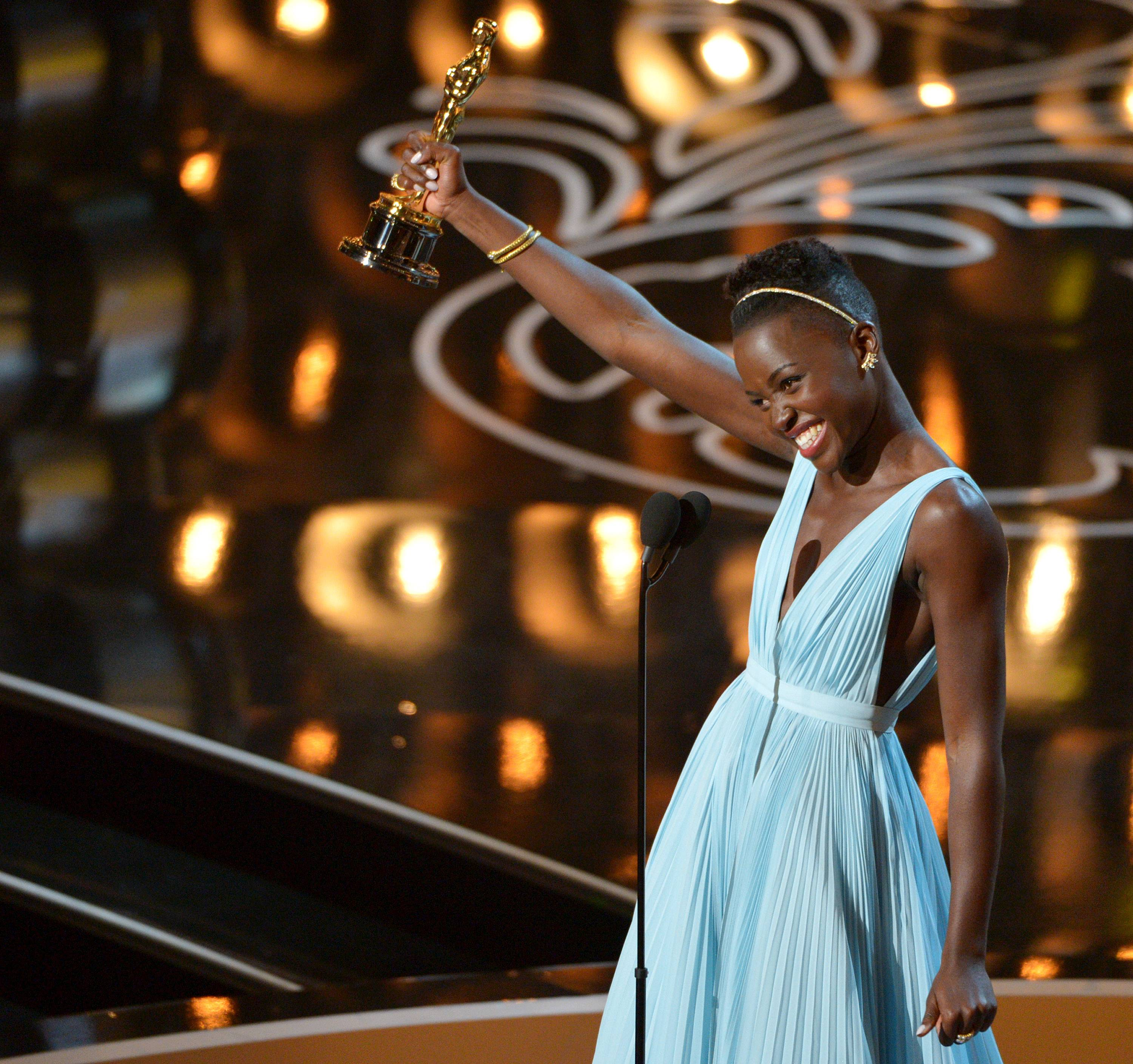 "Lupita Nyong'o accepts the award for best actress in a supporting role for ""12 Years a Slave,"" during the Oscars at the Dolby Theatre in Los Angeles."